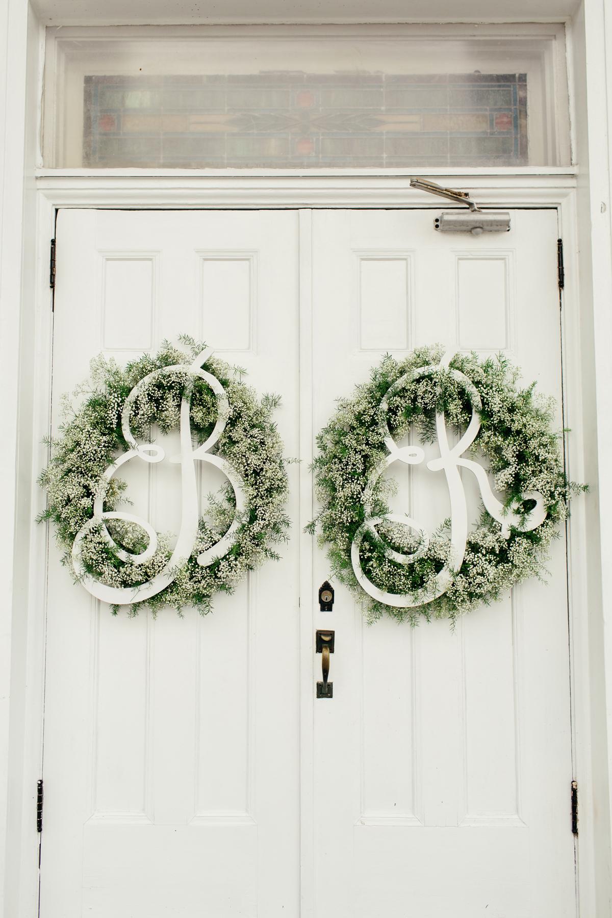 wedding wreaths monogramed hanging on white double doors