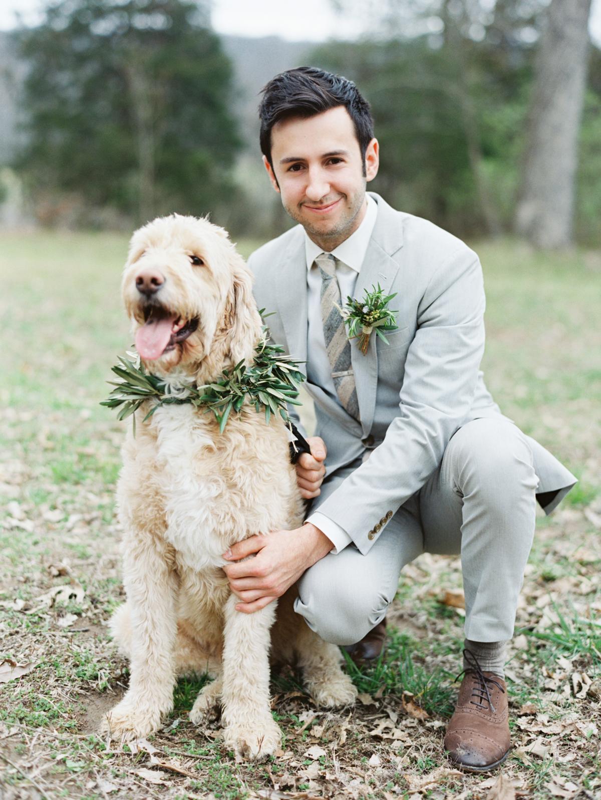 wedding wreath worn by dog sitting next to groom