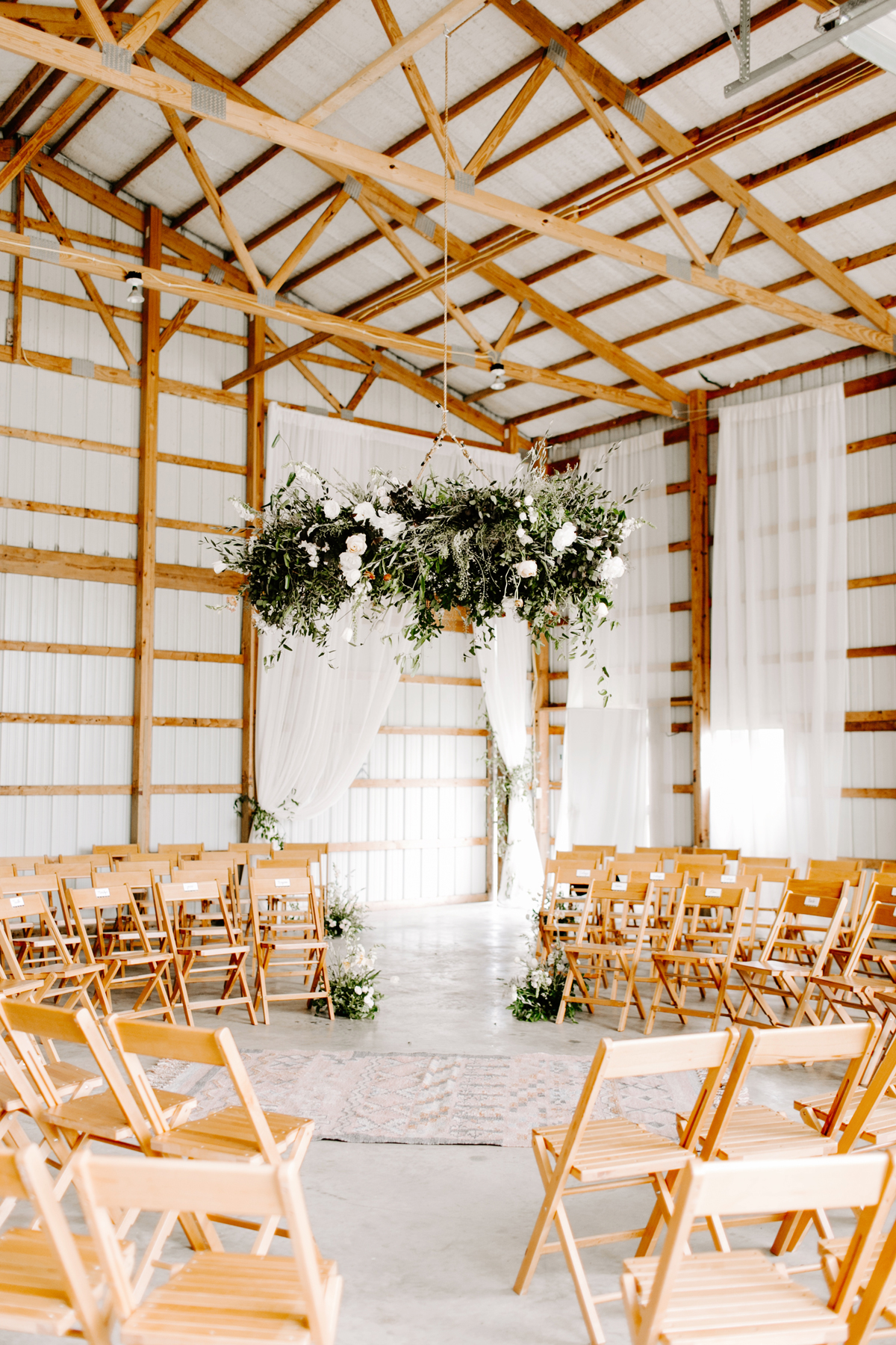 wedding wreaths foliage and roses hanging from exposed wood ceiling