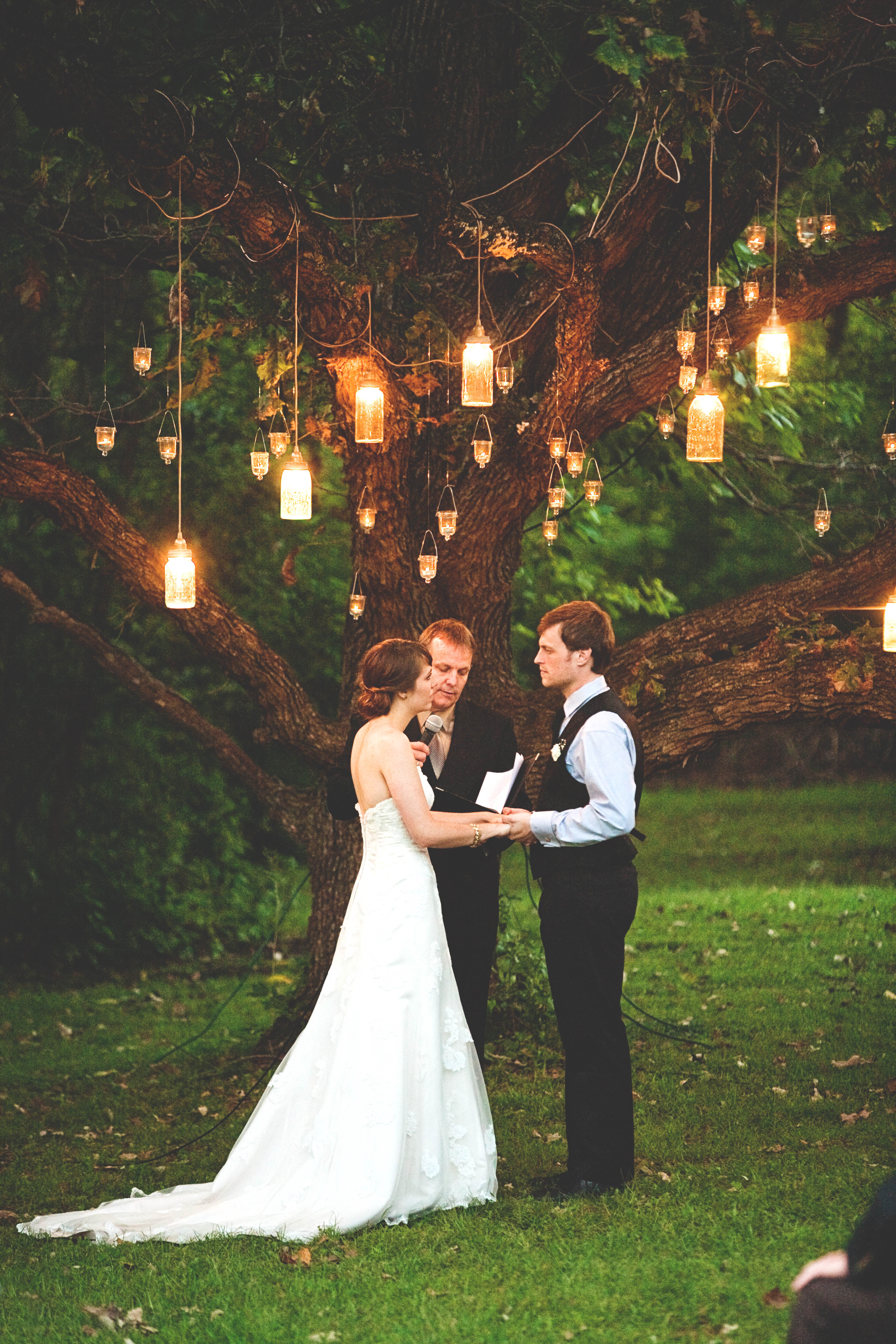mason jar lighting hanging from tree over couple