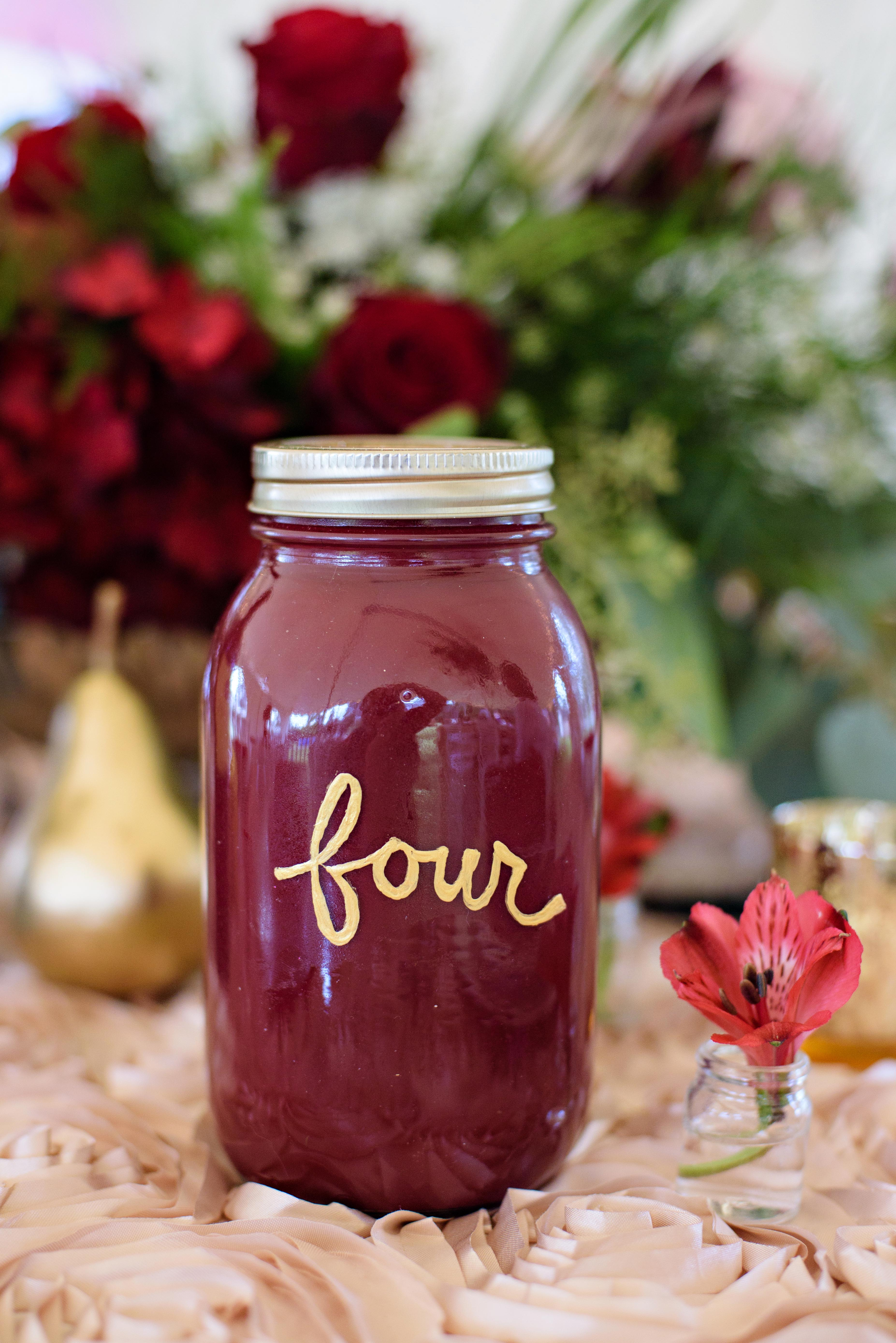 mason jar maroon table number four with floral decor