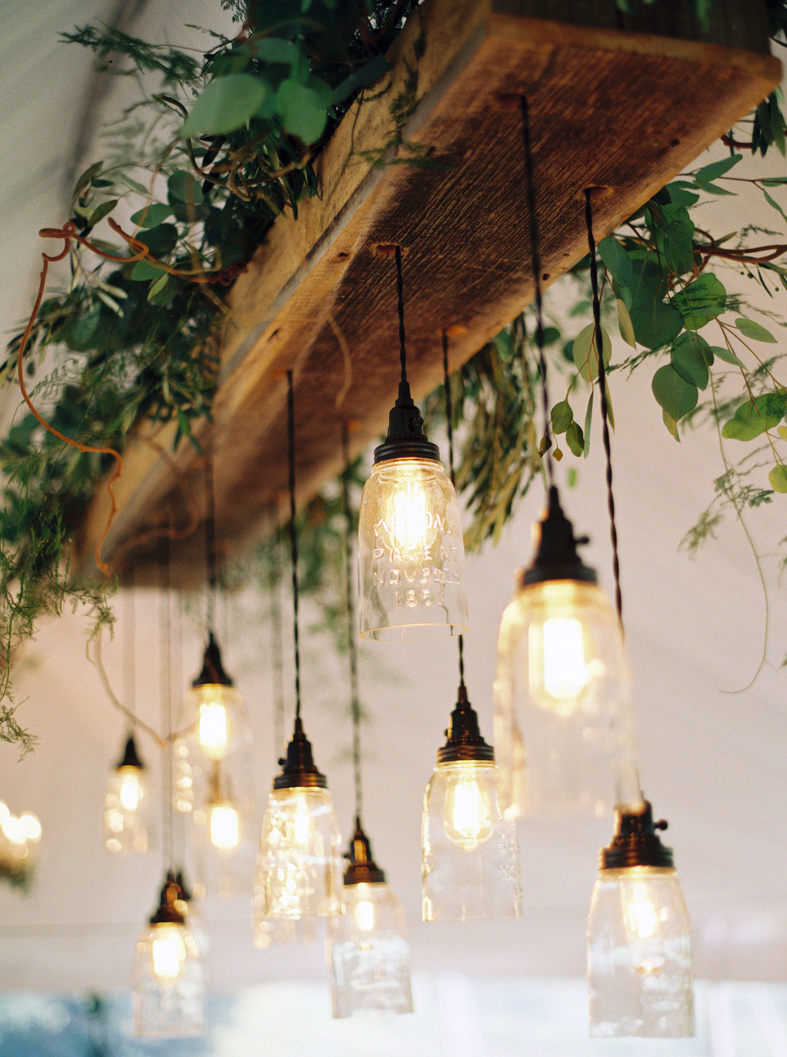 mason jar hanging lights from wood beam with greenery