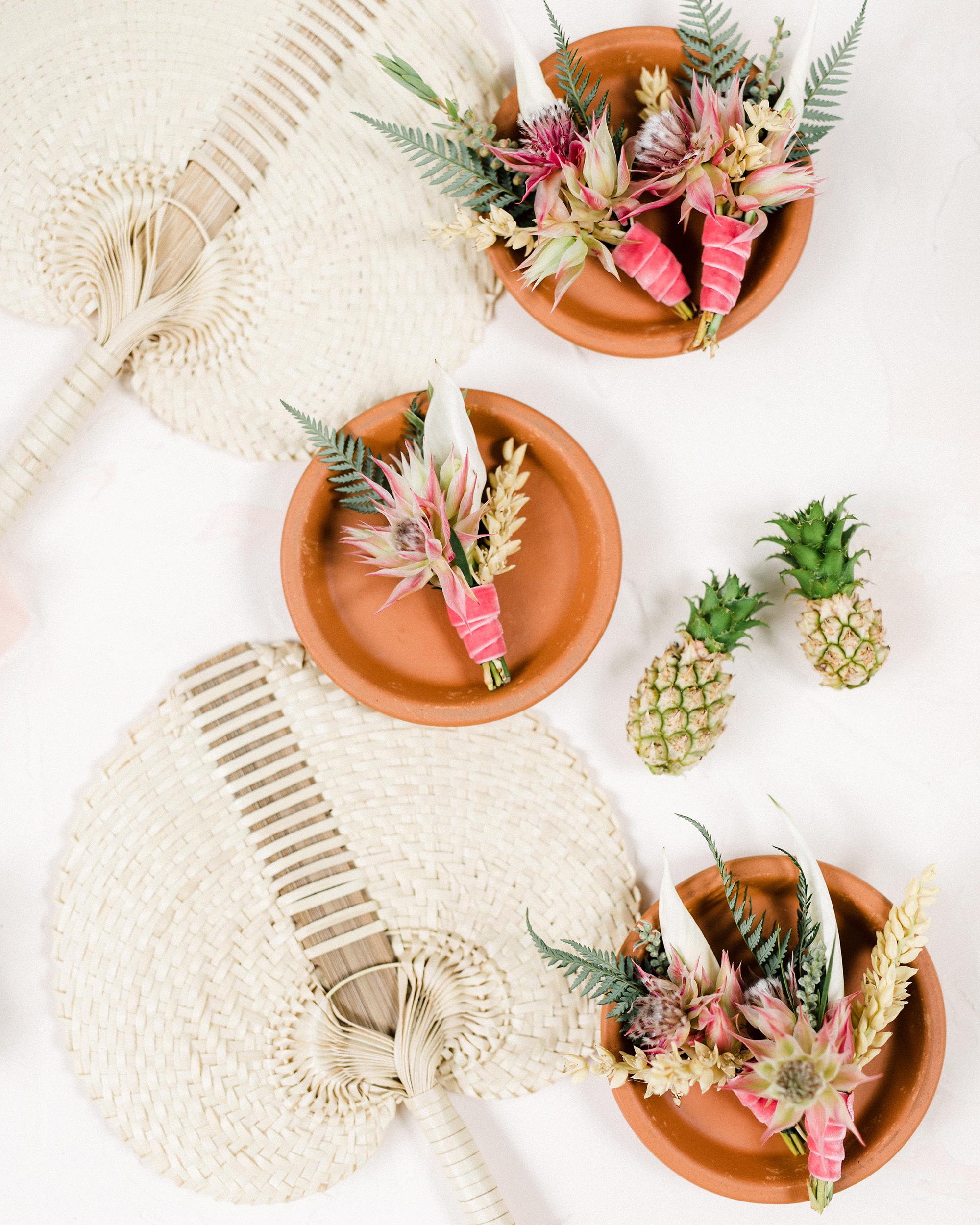 tropical wedding boutonnieres with protea and mini ferns