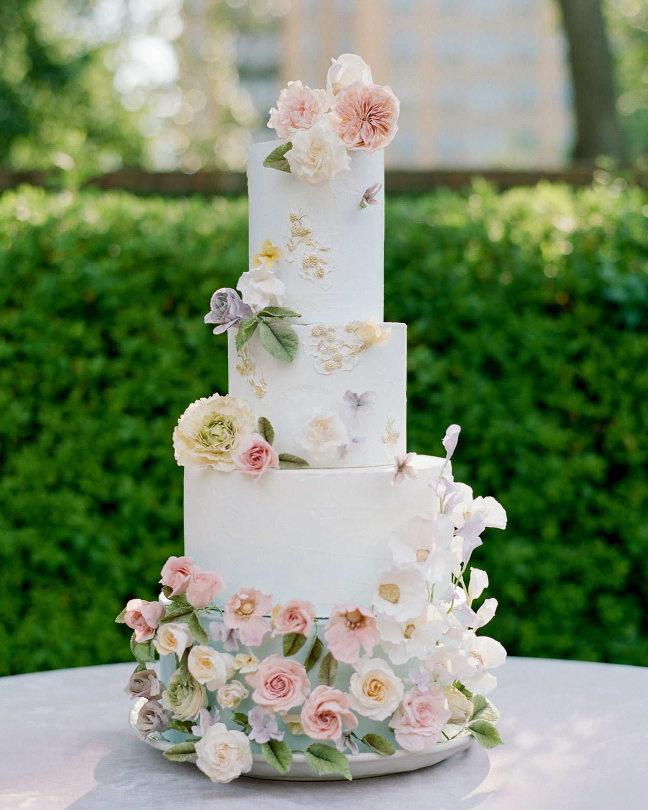 tall four tiered white wedding cake with floral decor