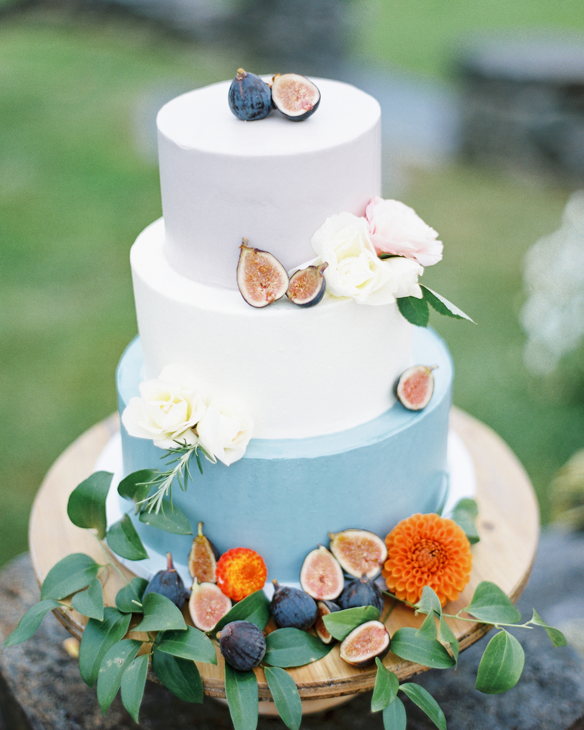 orange floral and blue fig accented three tiered wedding cake