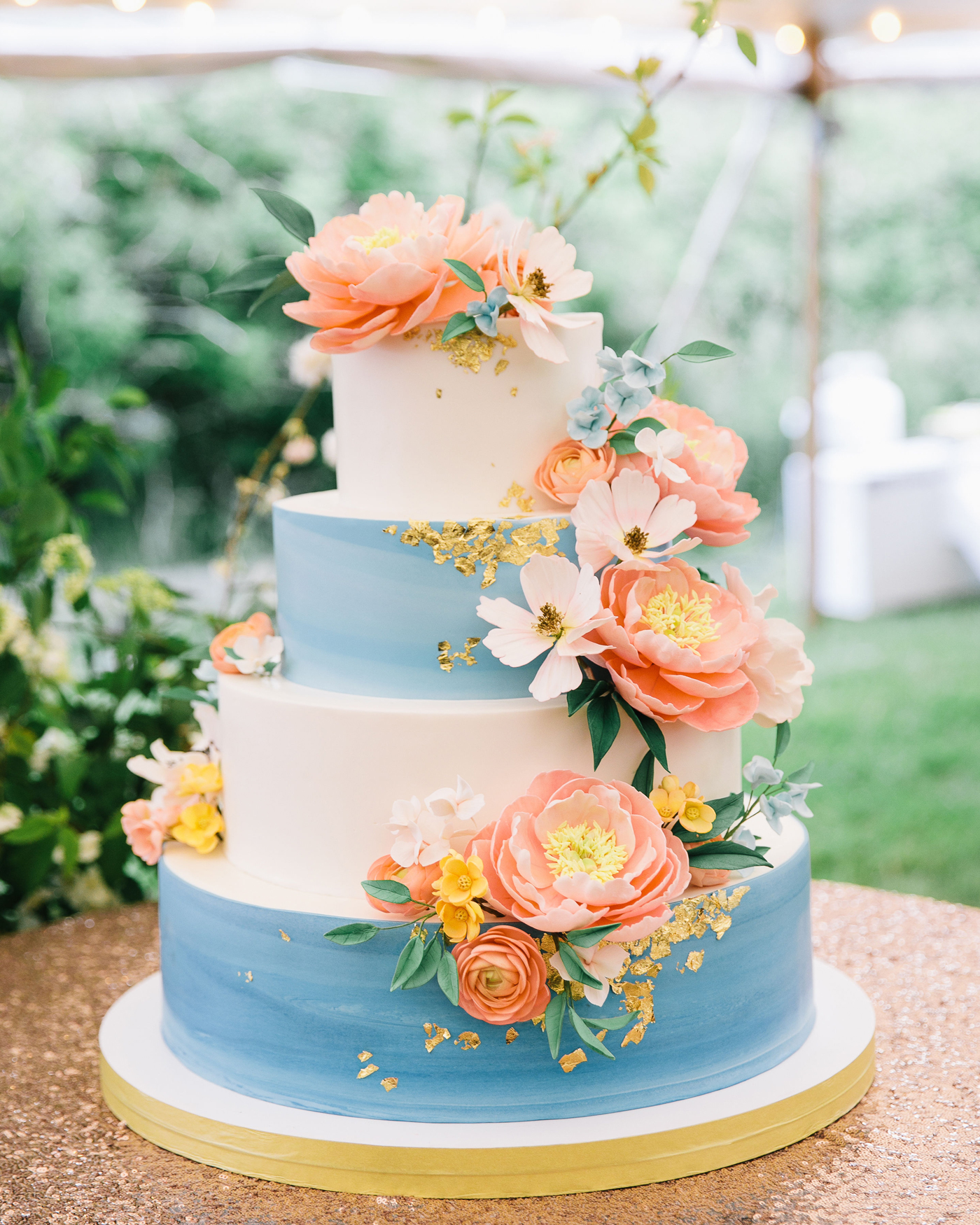 four tiered blue and white frosted wedding cake with pink and yellow floral accents