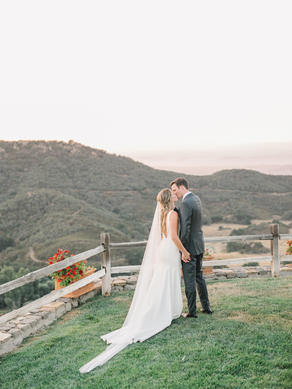 couple standing on hillside overlooking hillside