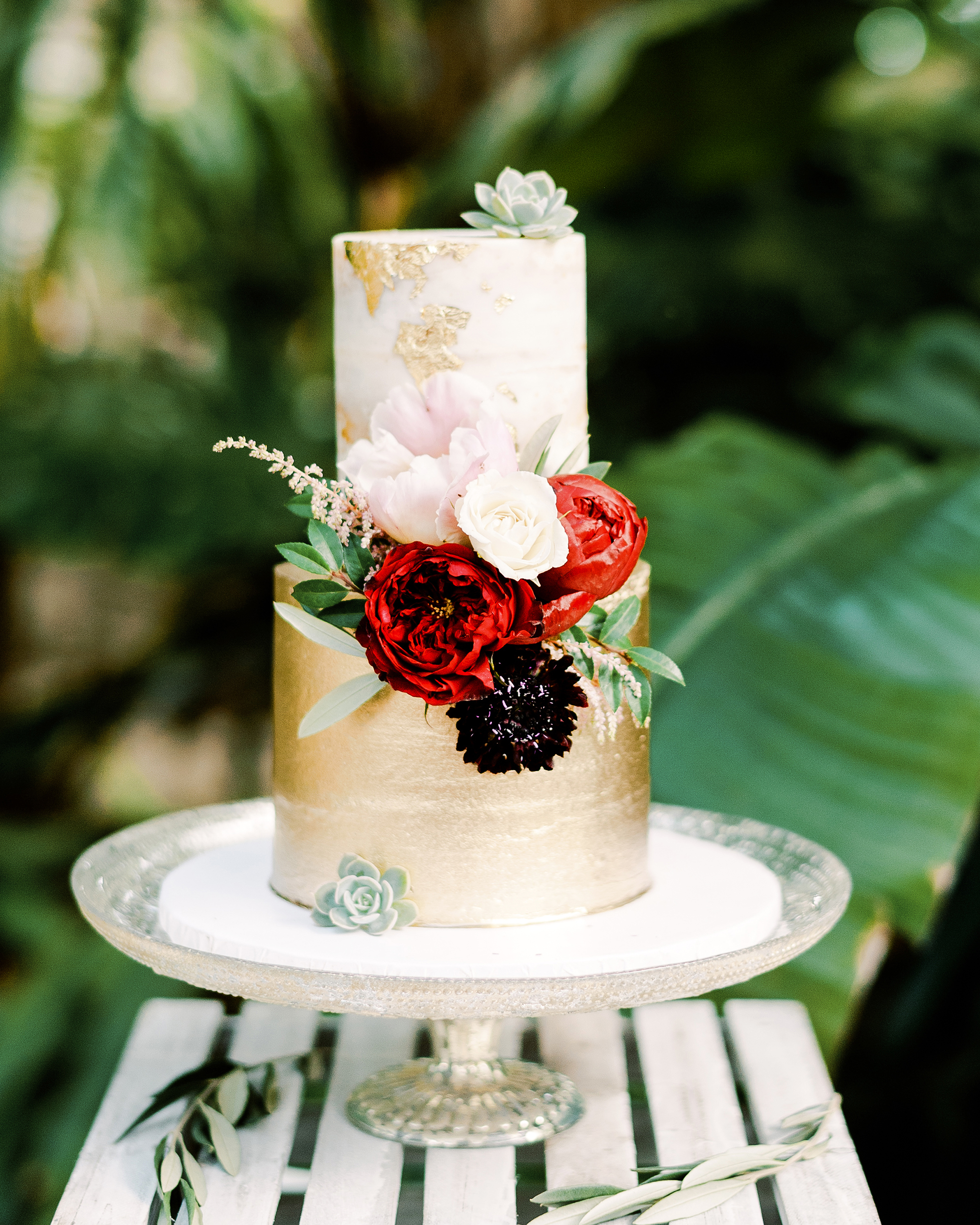 metallic gold wedding cake with red flowers
