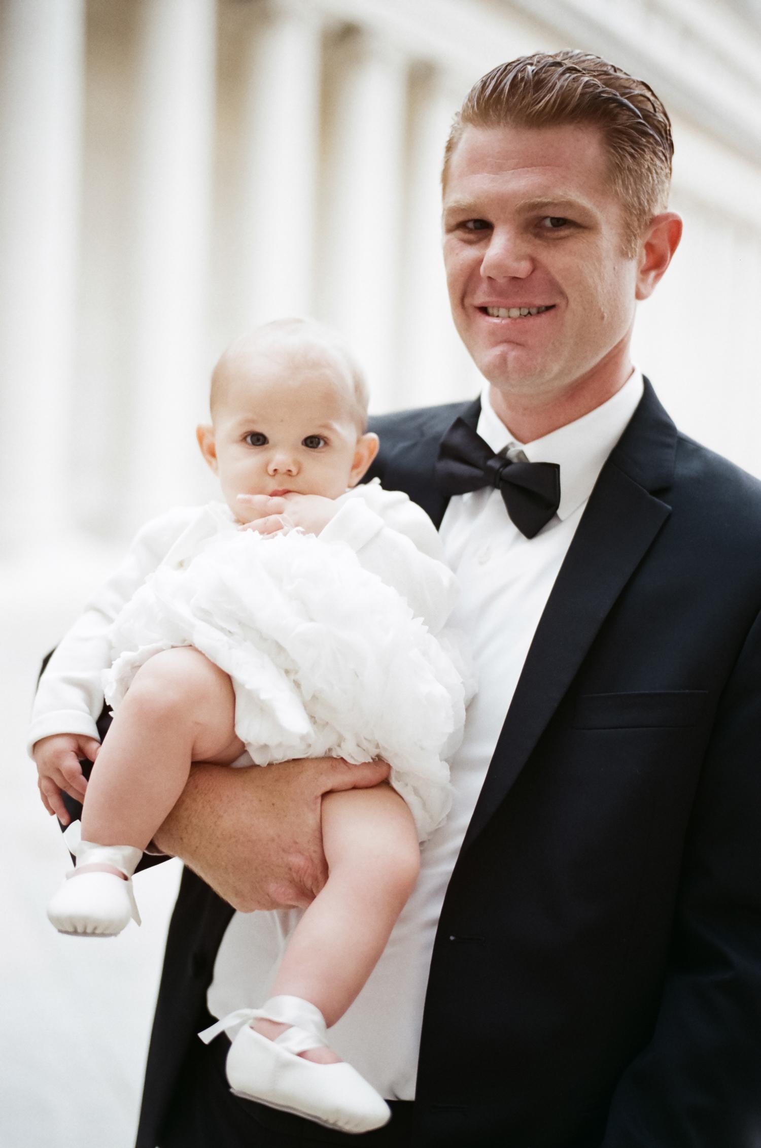 groom holding baby
