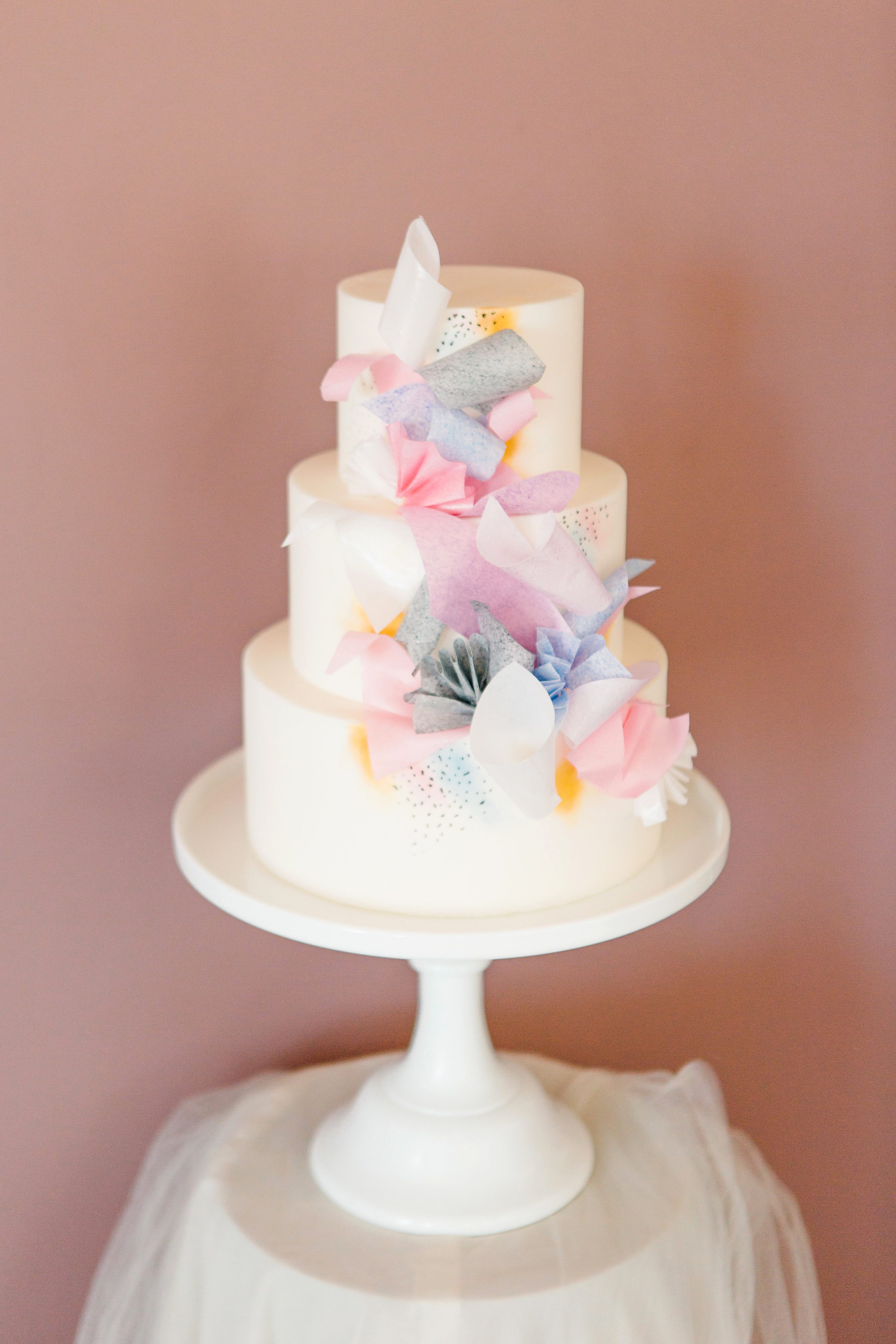 3-tier white cake decorated with pastel paper pieces