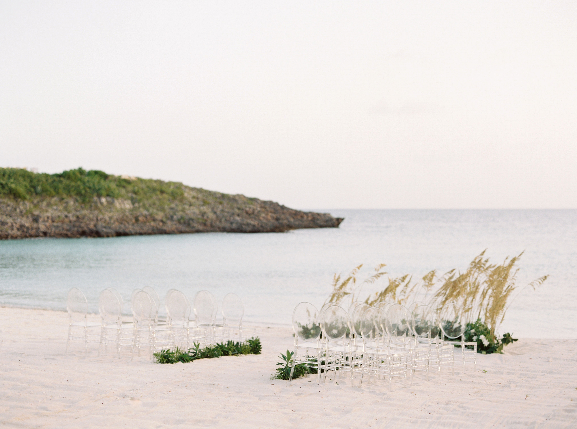 lucite chairs arranged on a beach