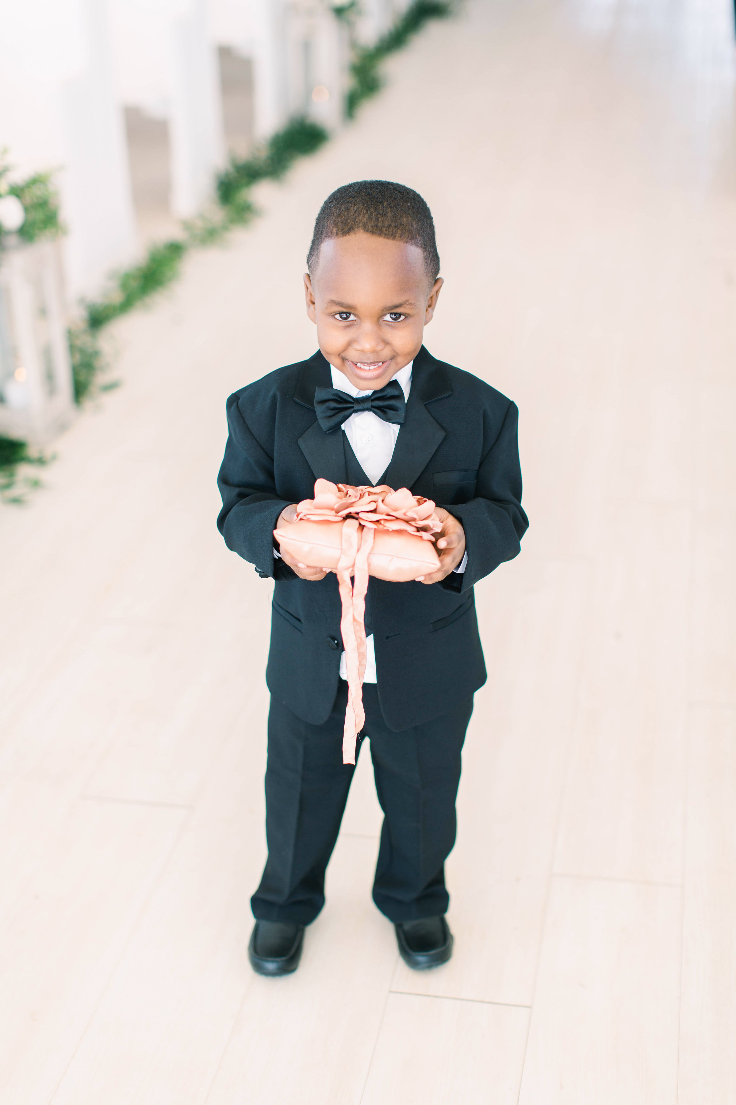 wedding young boy ring bearer with pink pillow