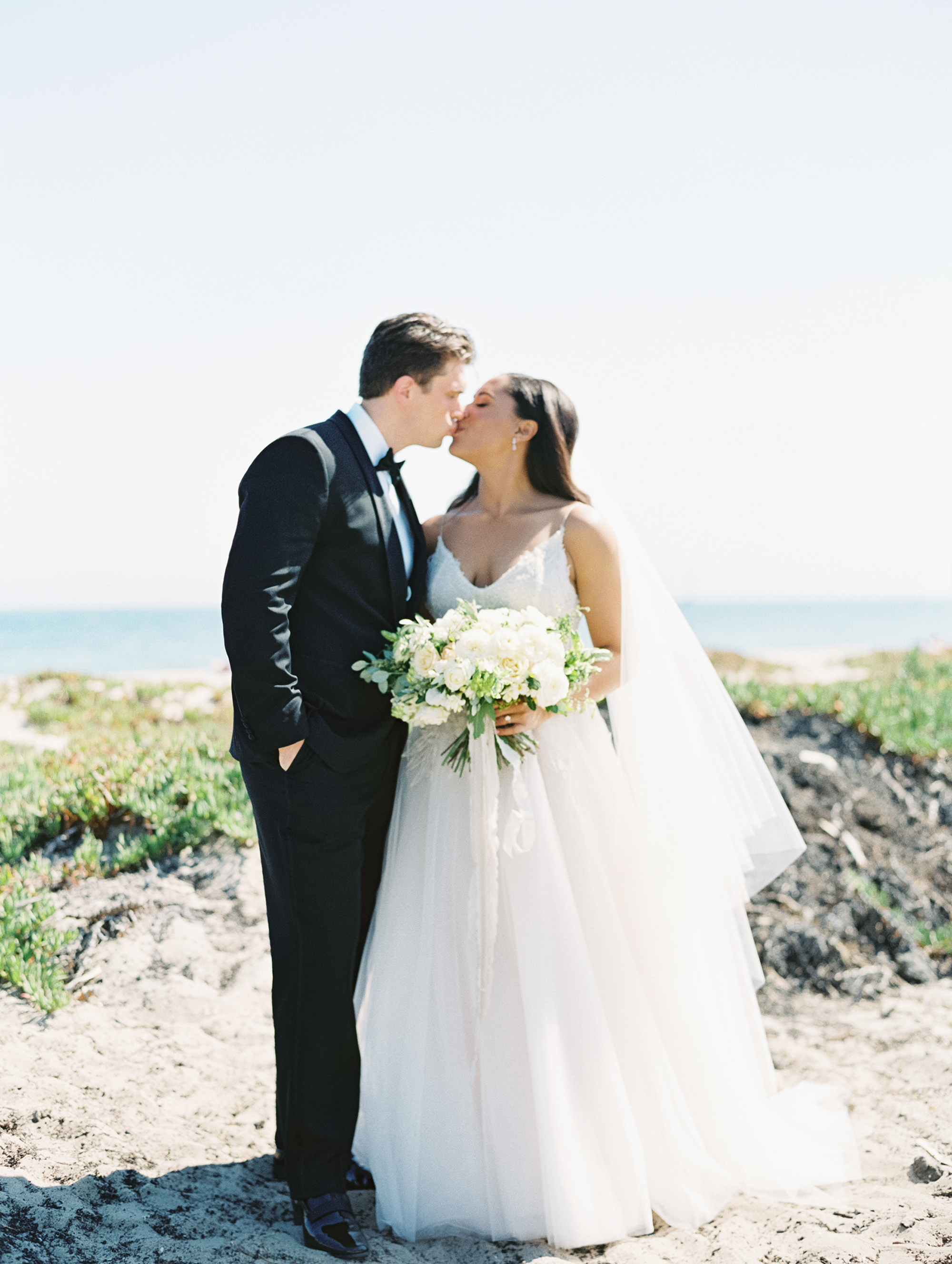 beach wedding dresses couple kissing on sandy walkway