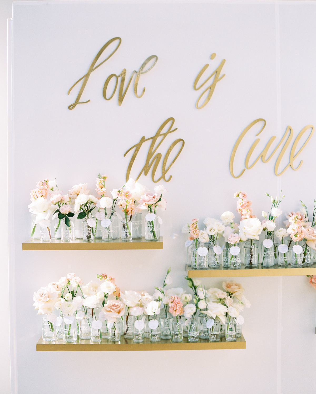 short stemmed floral arrangements in glass jars on floating shelves