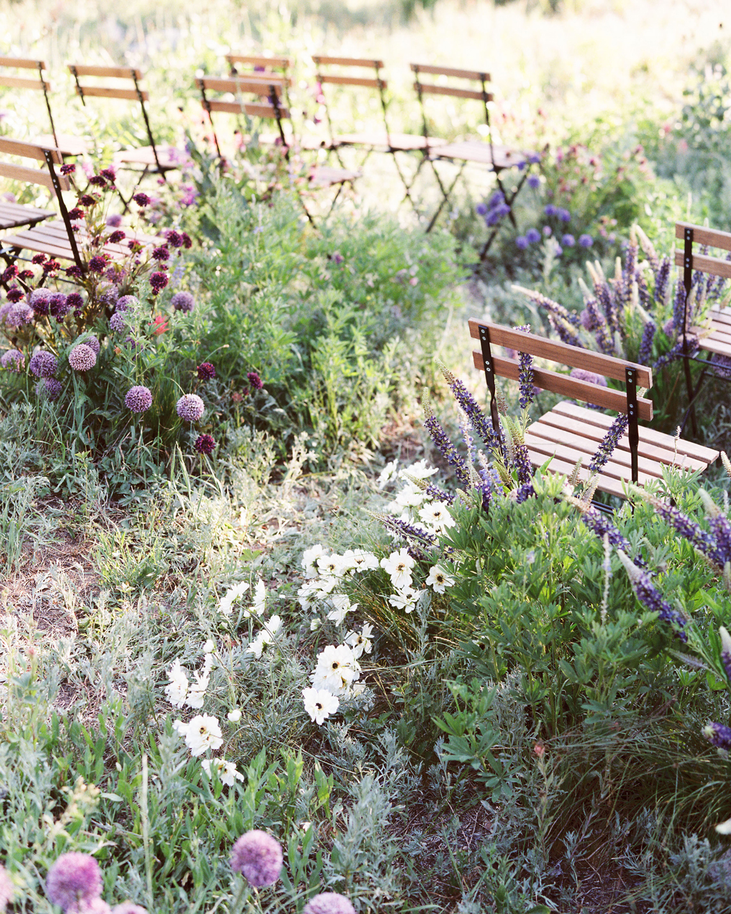 purple and white flowers with greenery wooden chairs
