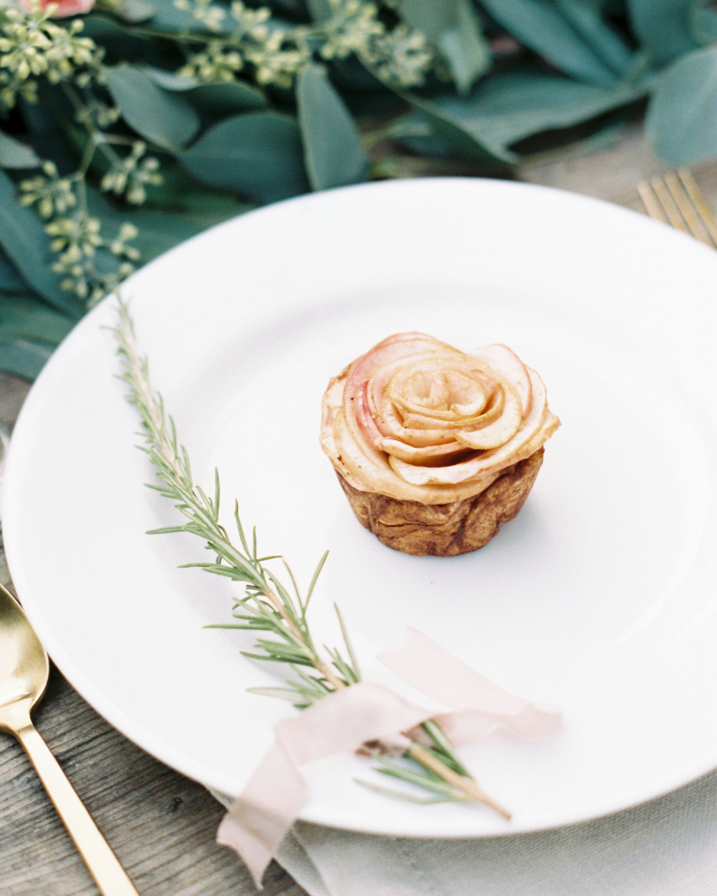 single dessert of white plate with greenery garnish and pink ribbon