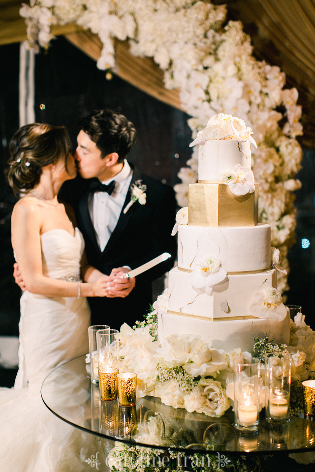 large wedding cake with gold and white tiers
