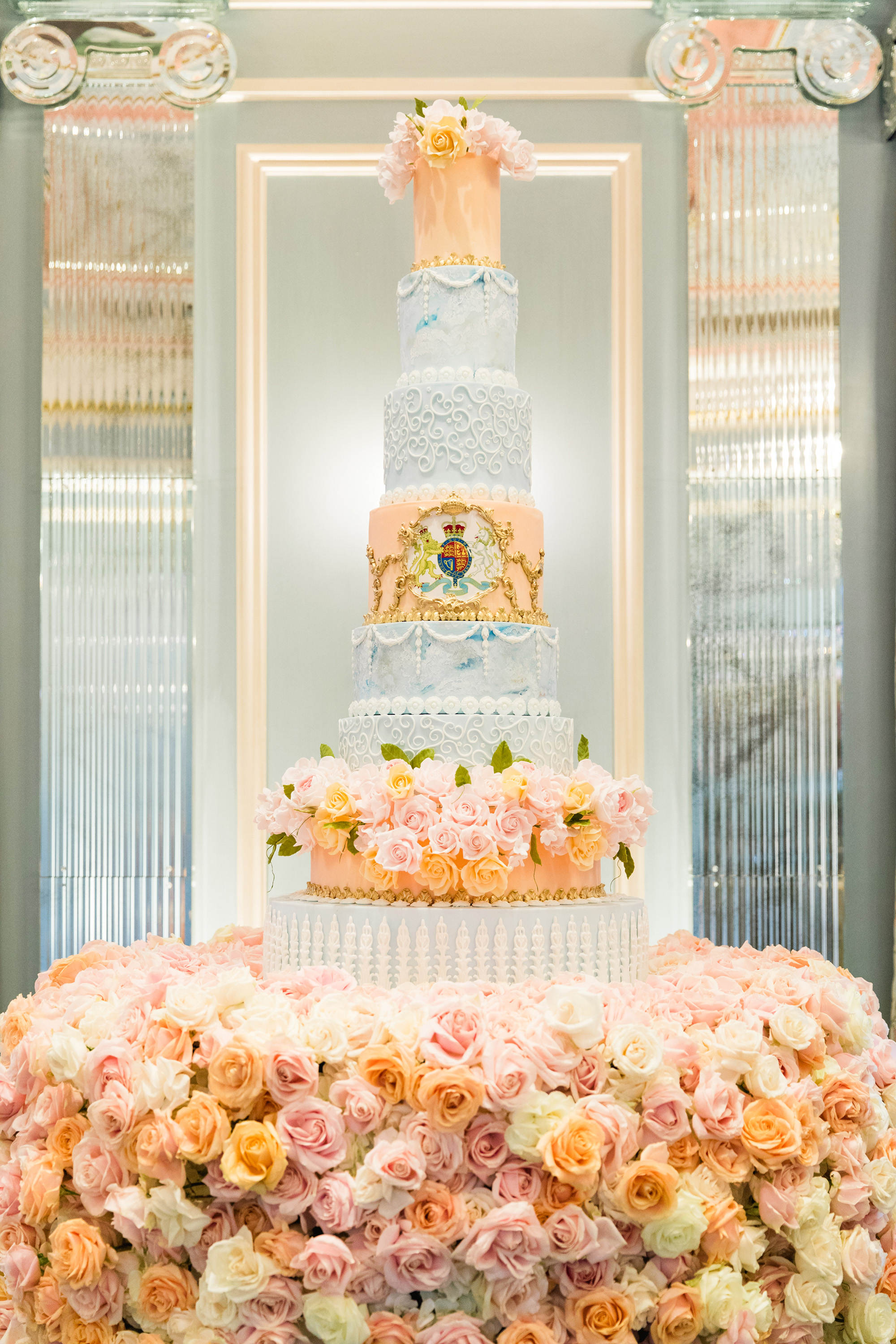 large blue and coral wedding cake with crest detail