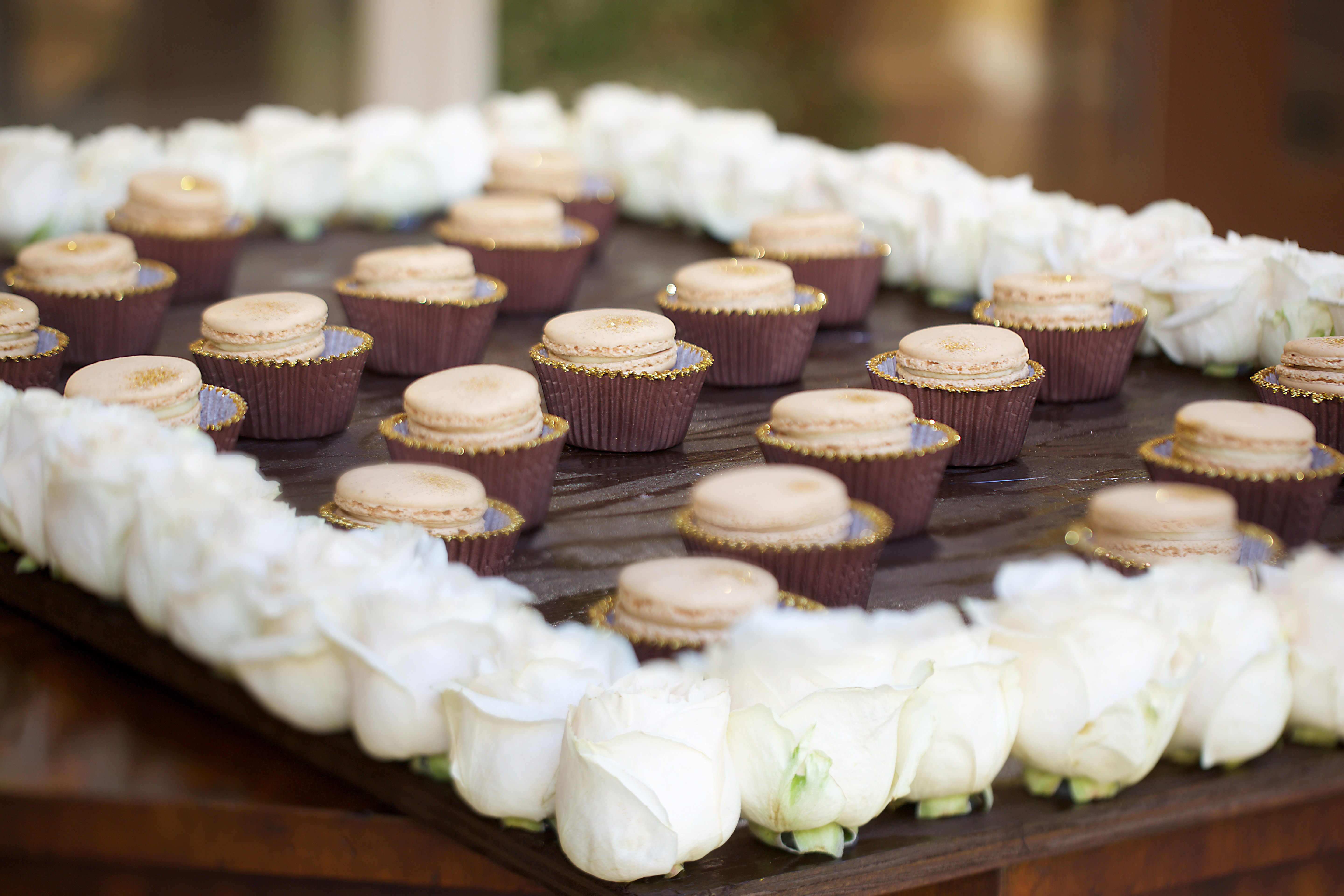Macarons with glitter on a board with roses