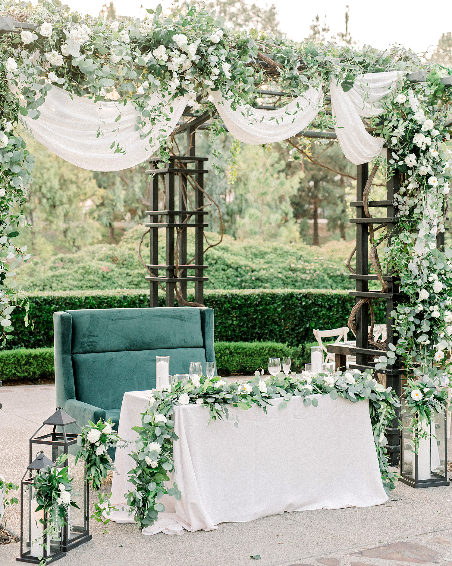 draped tulle over green loveseat at sweetheart table
