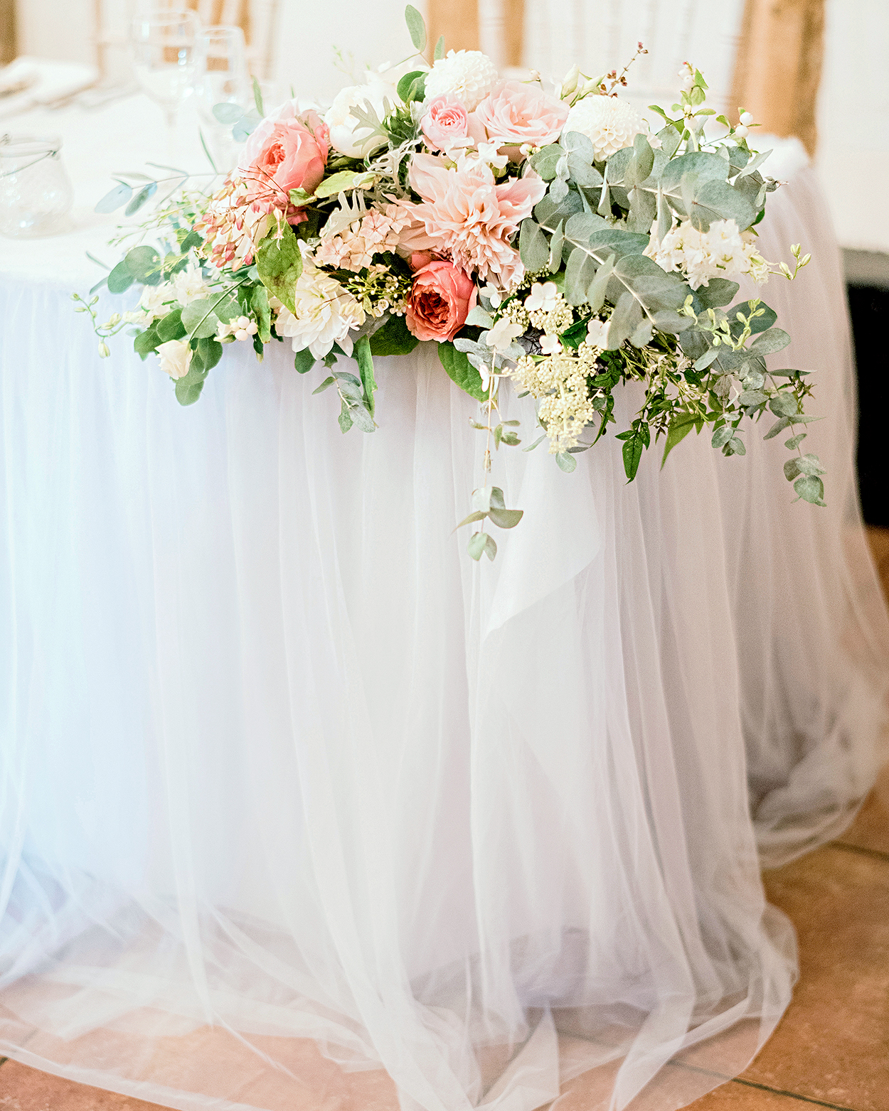table topped with tulle overlay and lush florals