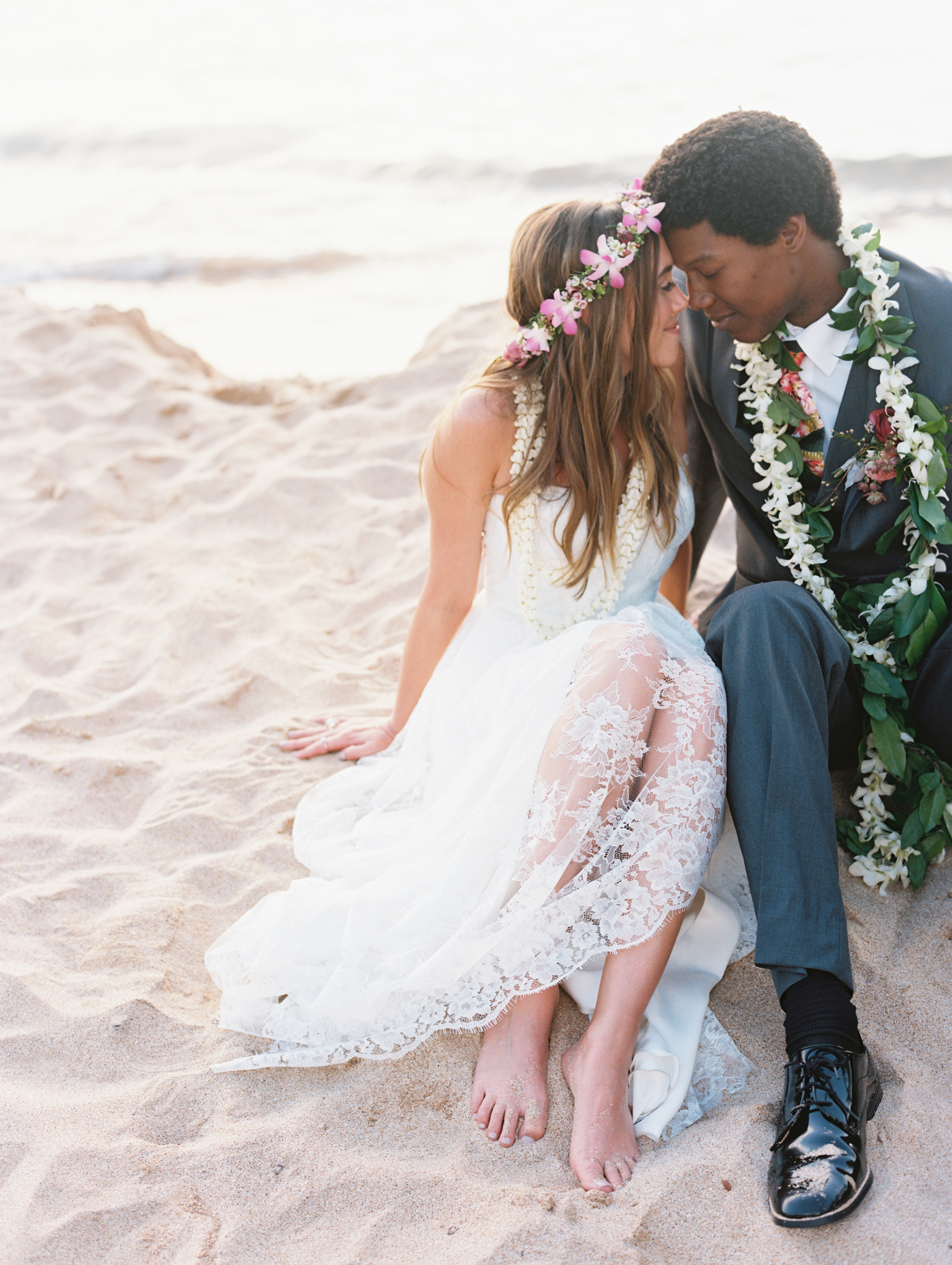 Bride and Groom Sitting on the Sand at the Beach