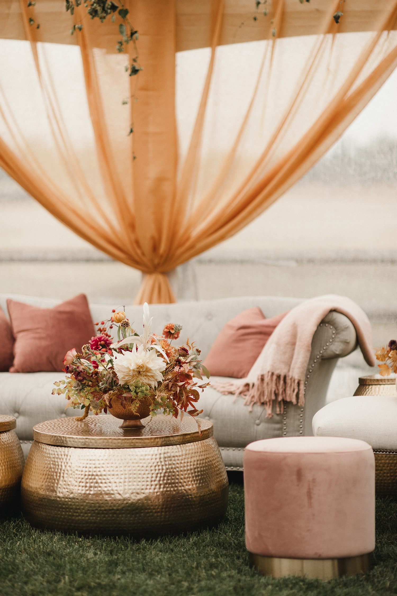 wedding lounge beige and orange couch and flowers