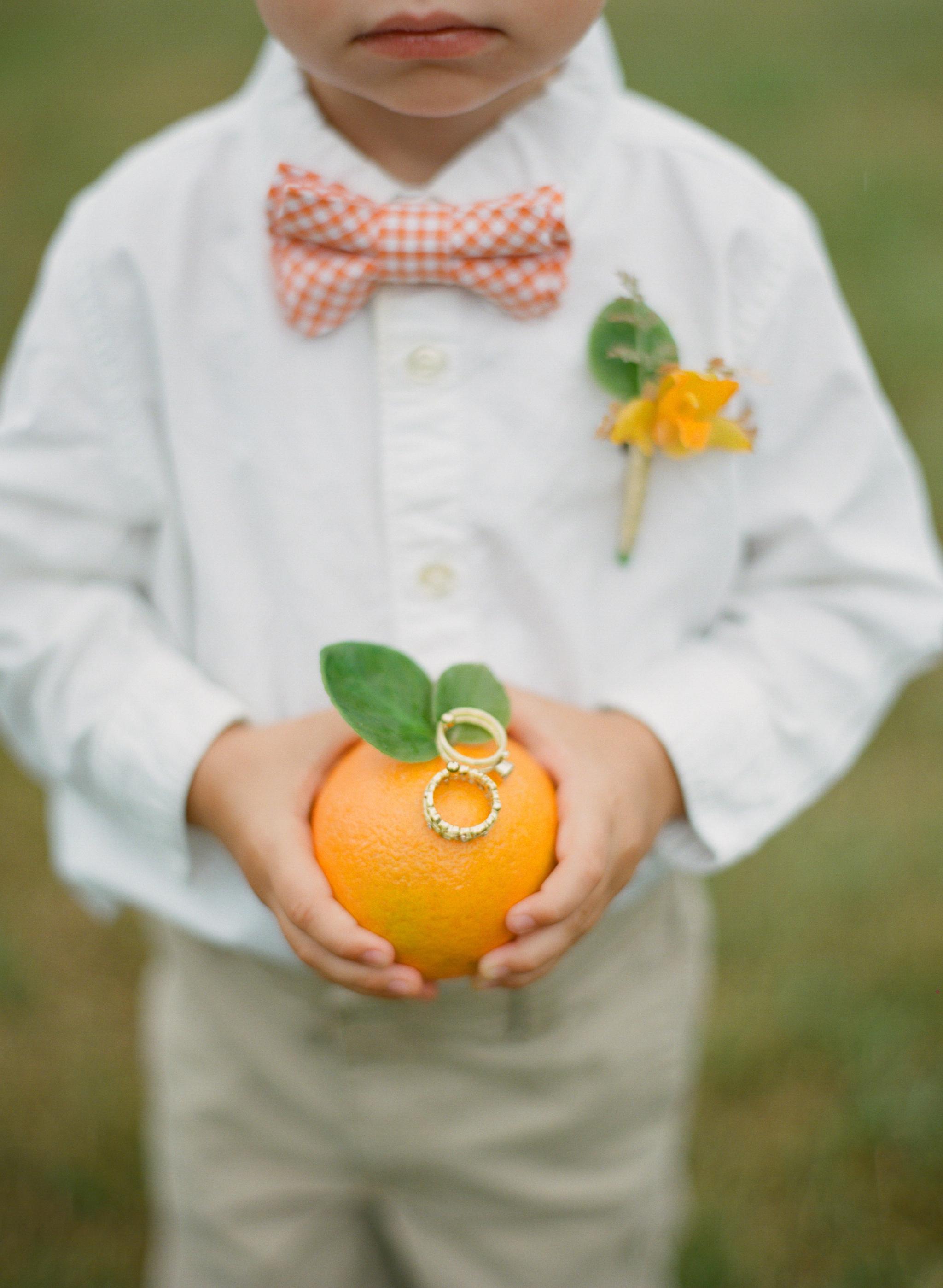 ring bearer holding rings on orange