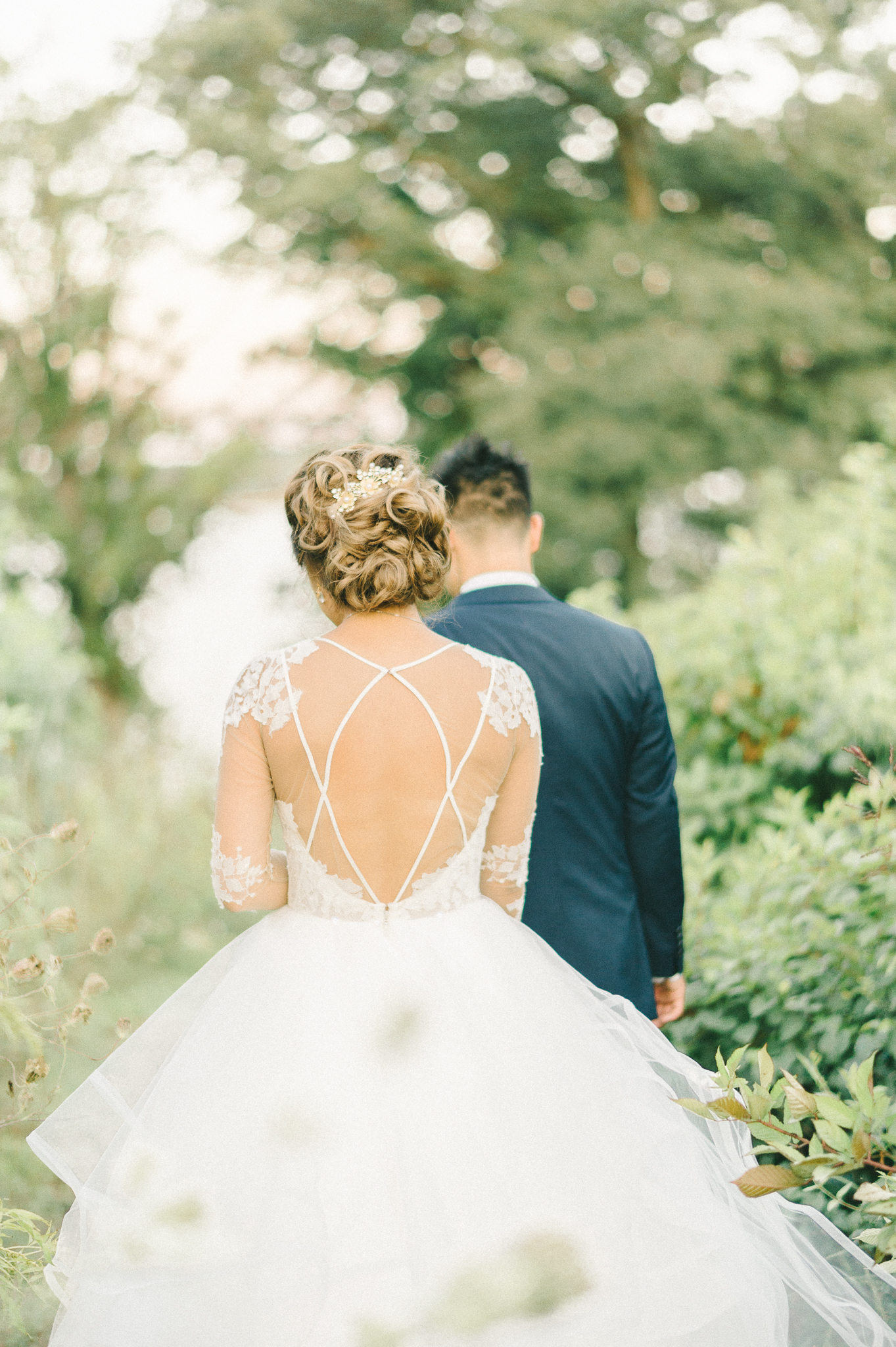 A Bride with an Illusion-Back Wedding Dress Walking with Her Groom