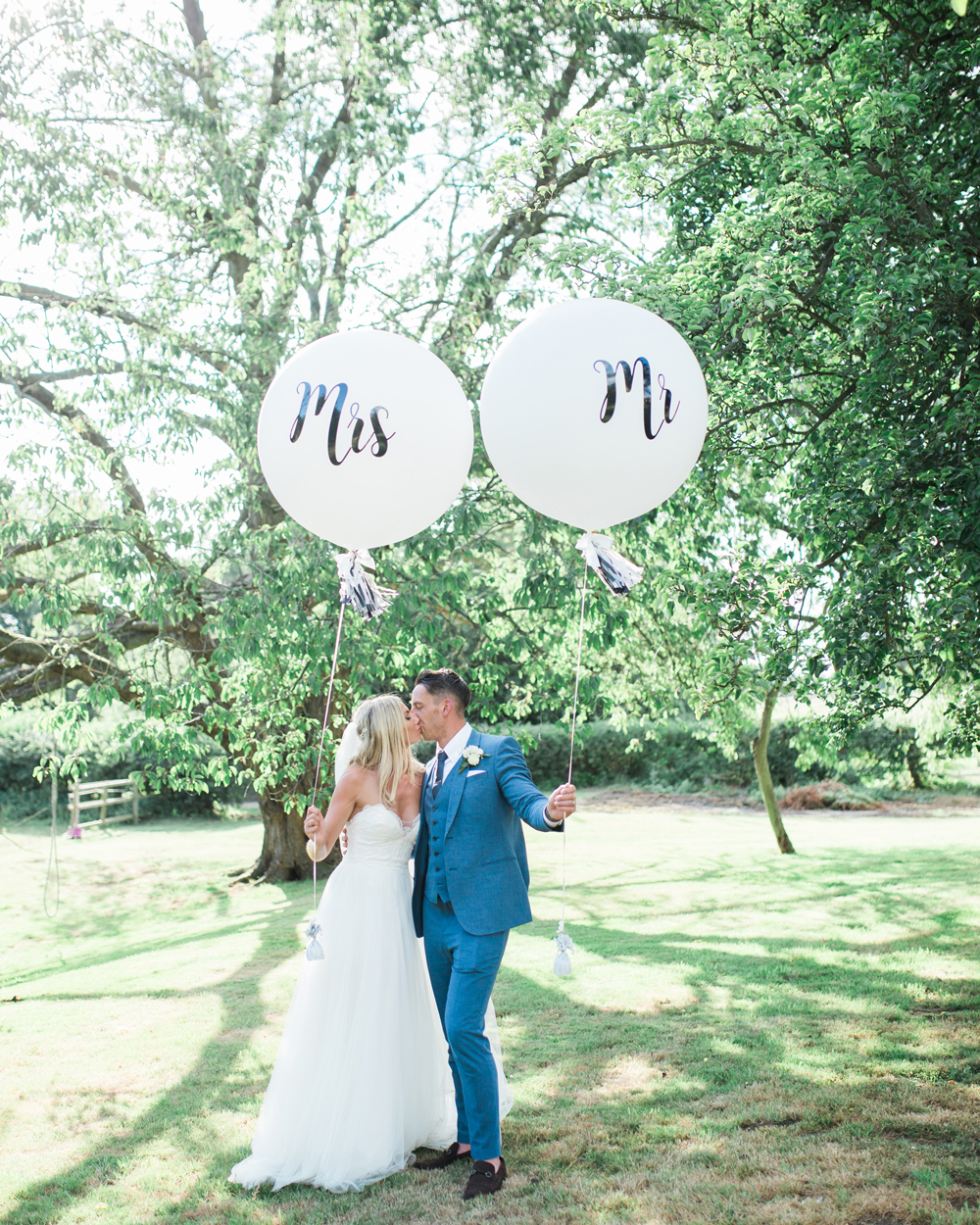 bride and groom holding white balloons with Mr and Mrs written