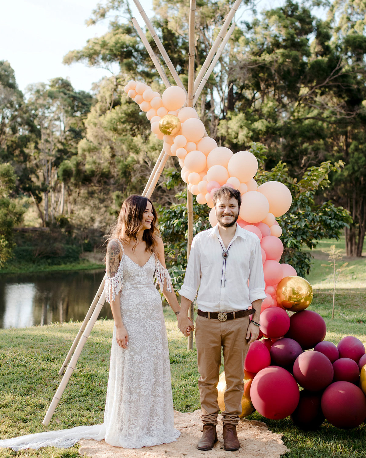 bride and groom standing next to wooden triangle ceremony arch covered in balloons