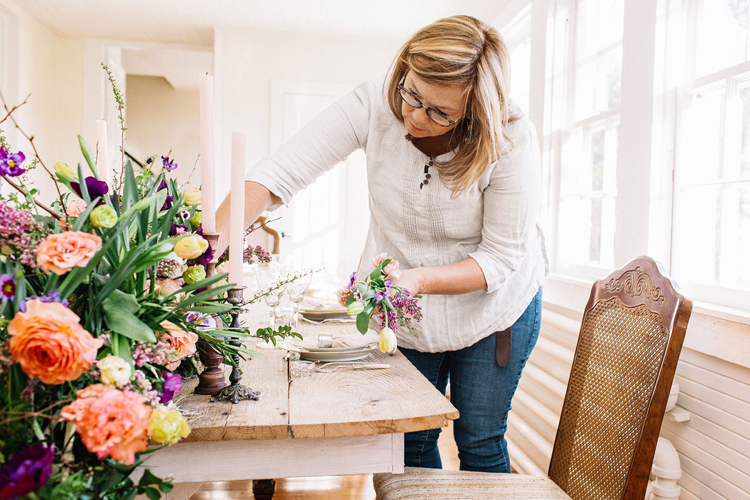 Holly Heider arranging floral centerpiece