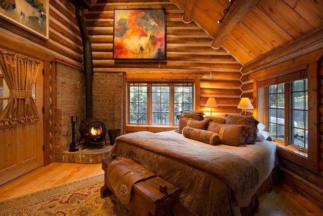 dude ranch honeymoon triple creek ranch log cabin bed fireplace