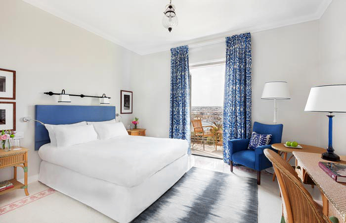 honeymoon destinations phoenicia blue white hotel room bed curtains