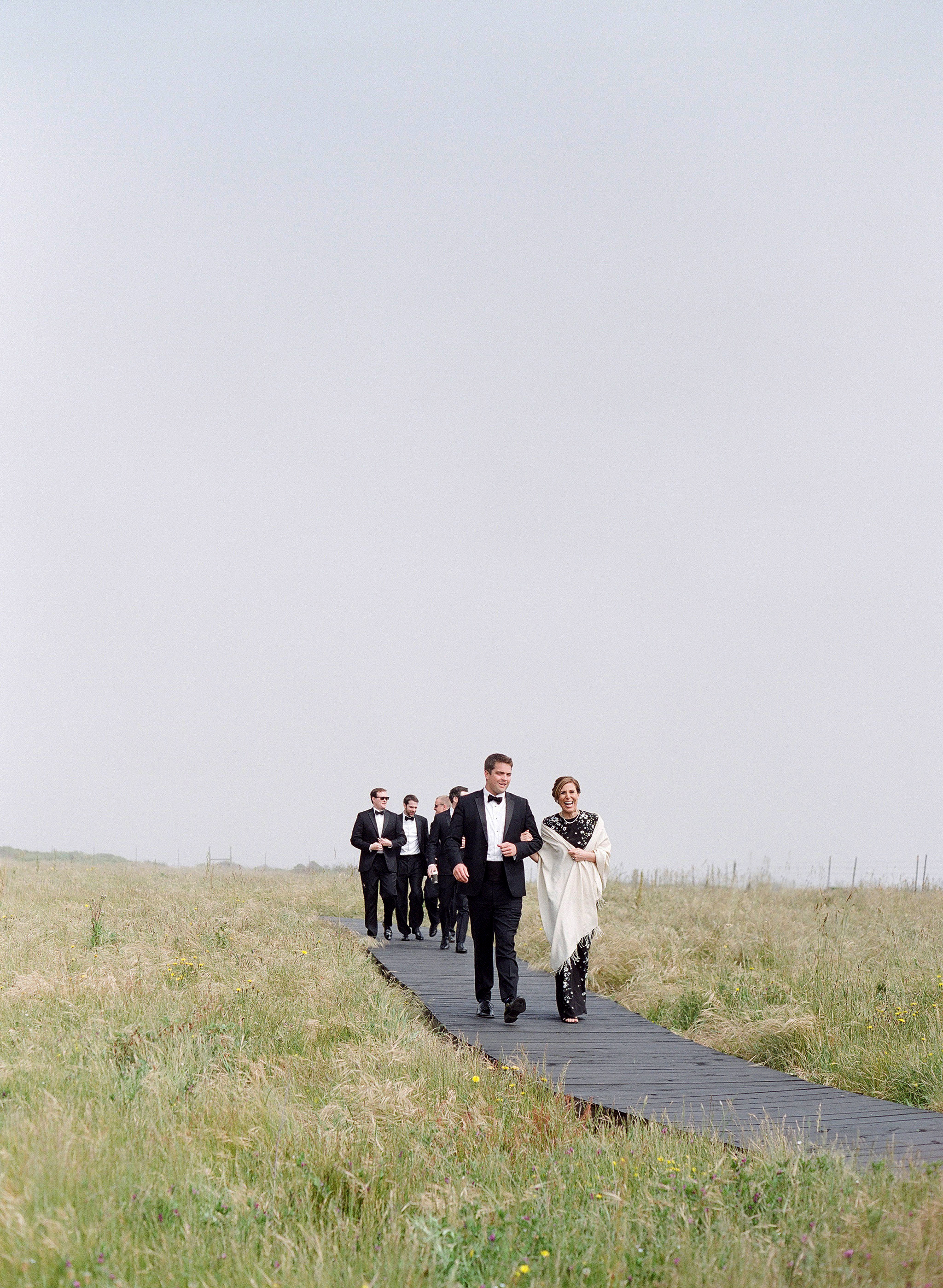 whitney zach wedding guests walking down wooden path in field