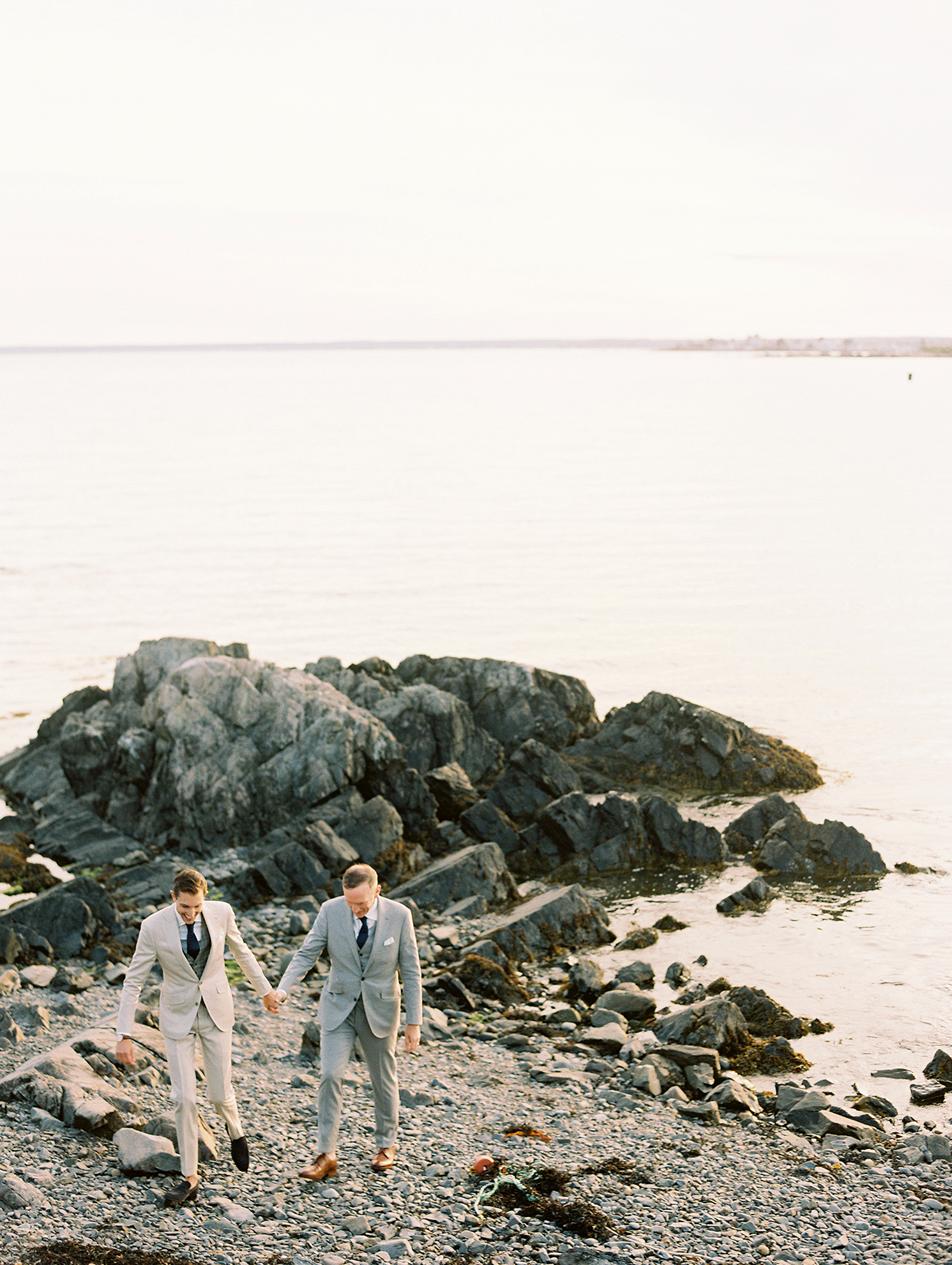 charles andrew wedding grooms on rocky shoreline