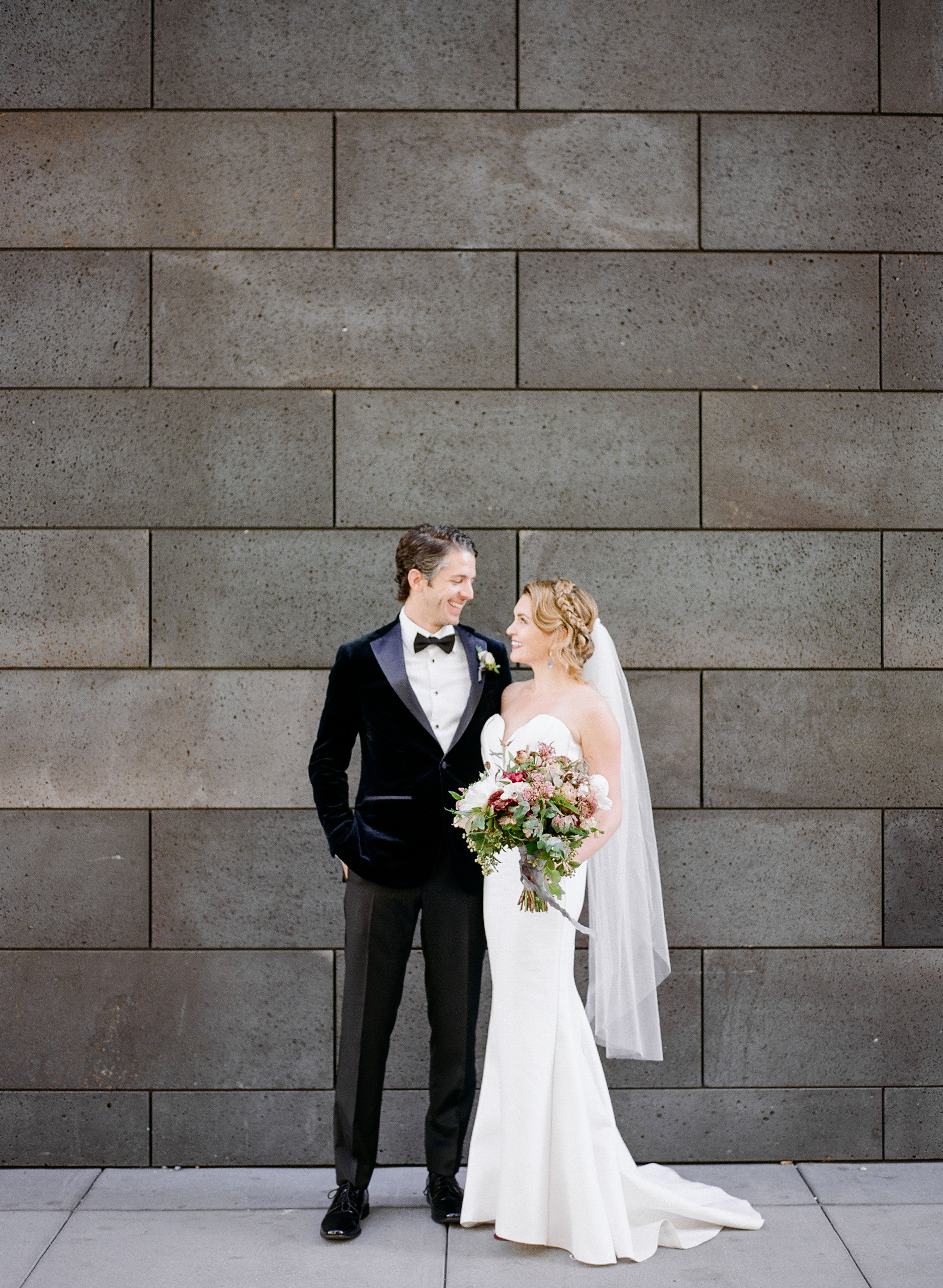 katie andre wedding couple gazing at each other gray brick wall