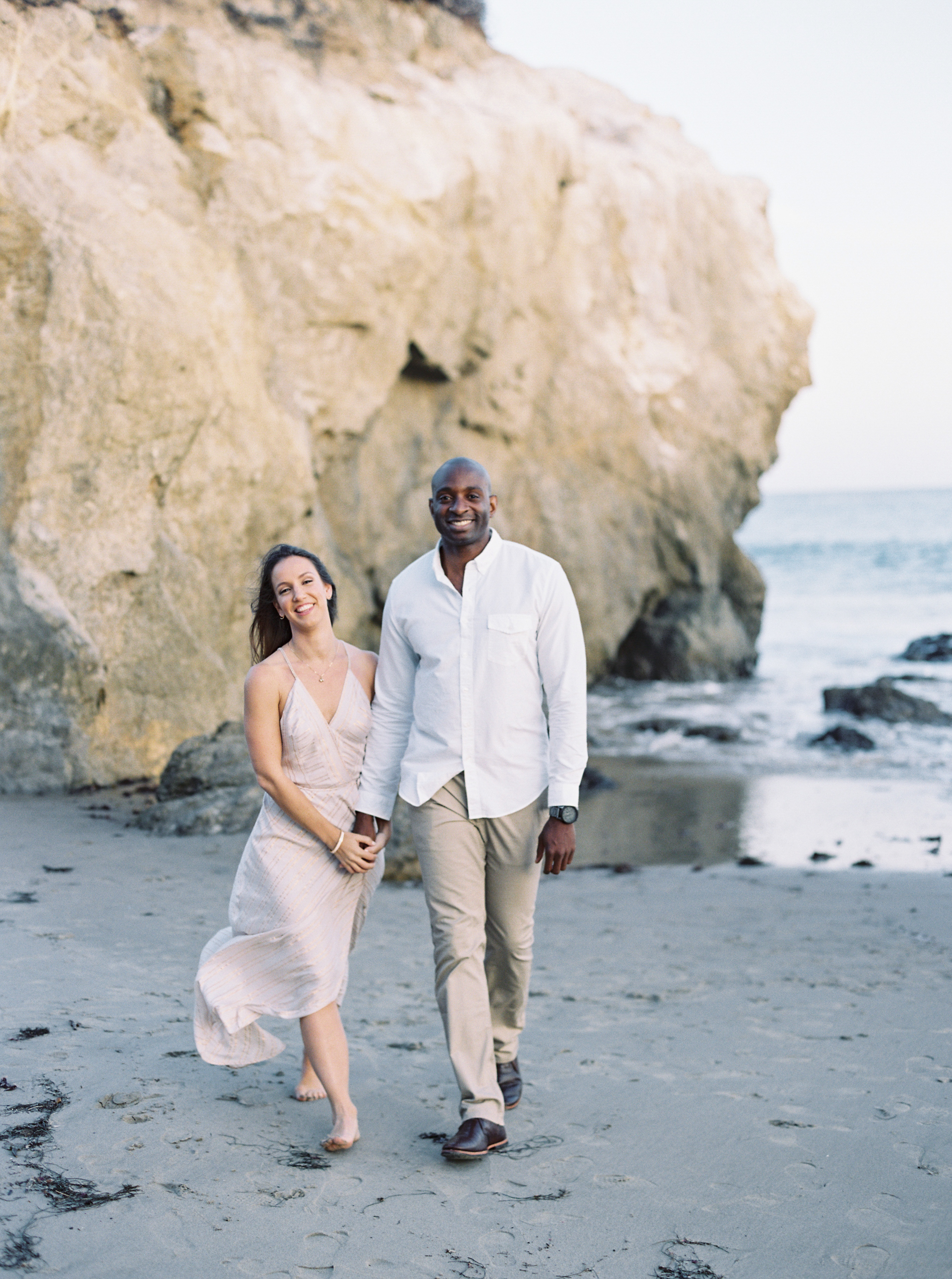 couple walking on beach outdoor engagement photos