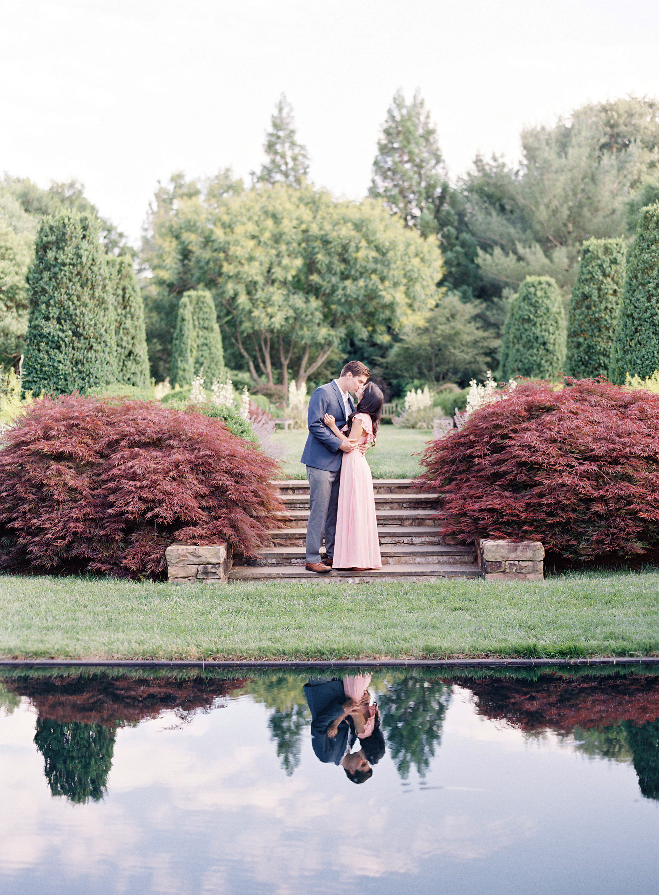 couple kissing by pool outdoor engagement photos