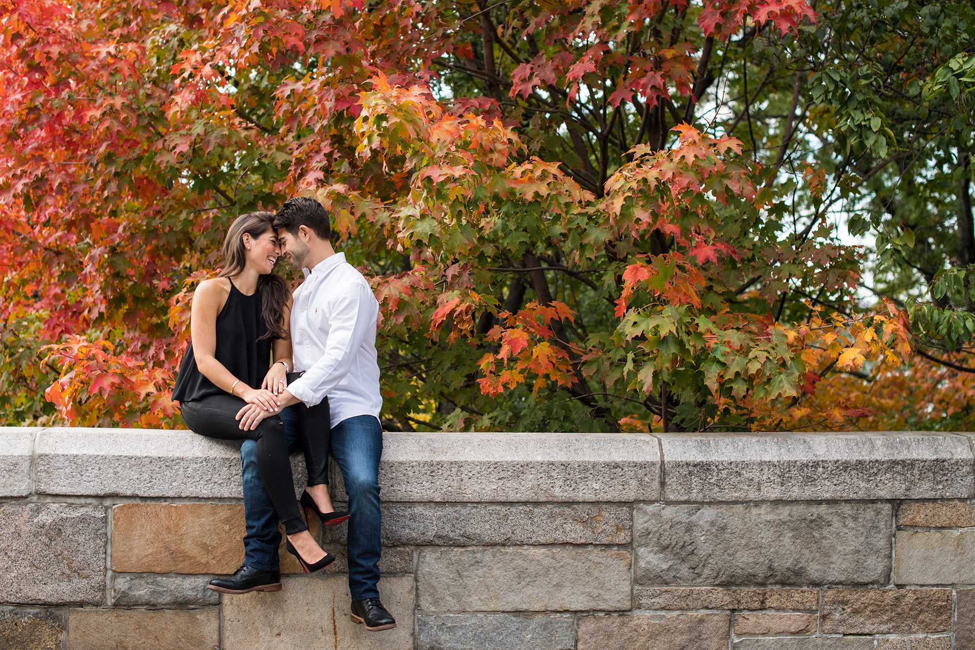 couple on ledge with leaves outdoor engagement photo