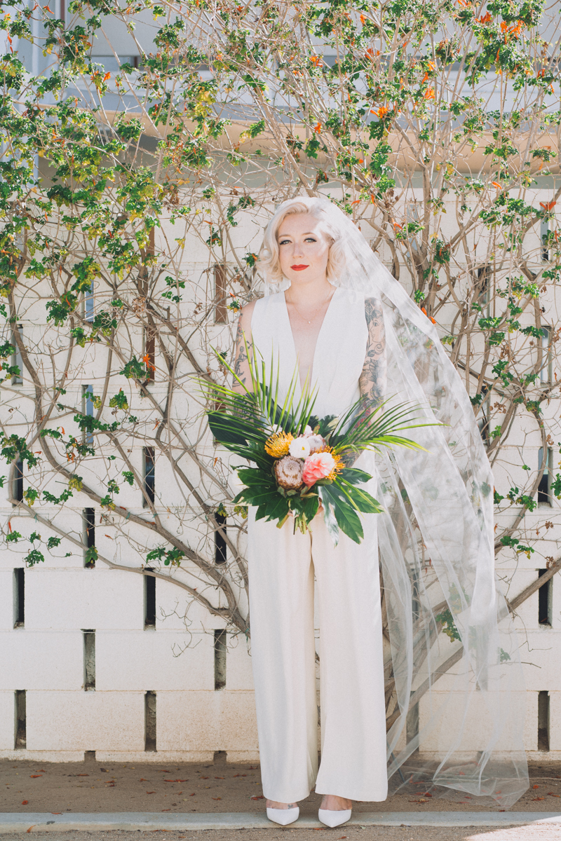 bride in jumpsuit holding bouquet