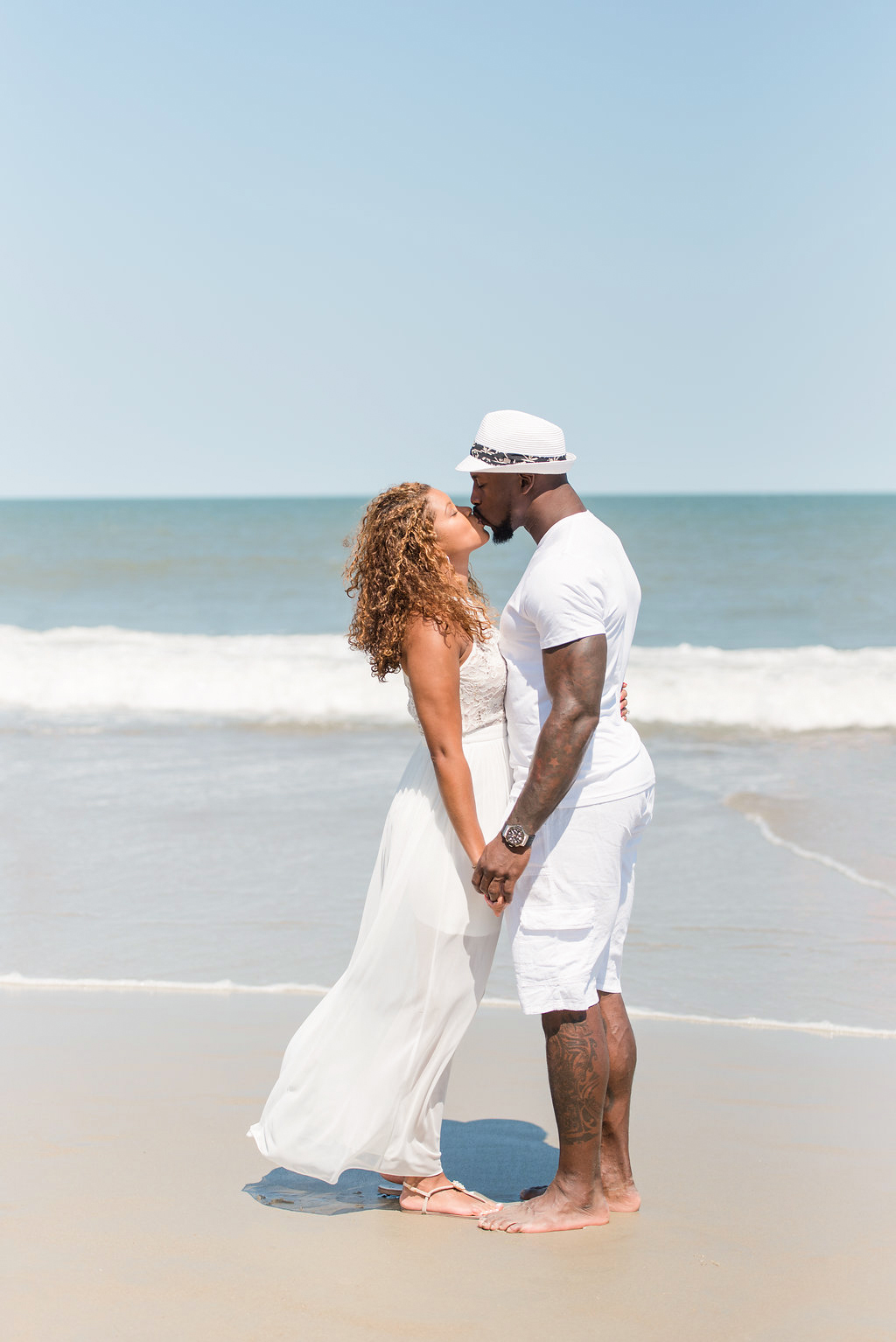 couple in white kissing at seashore