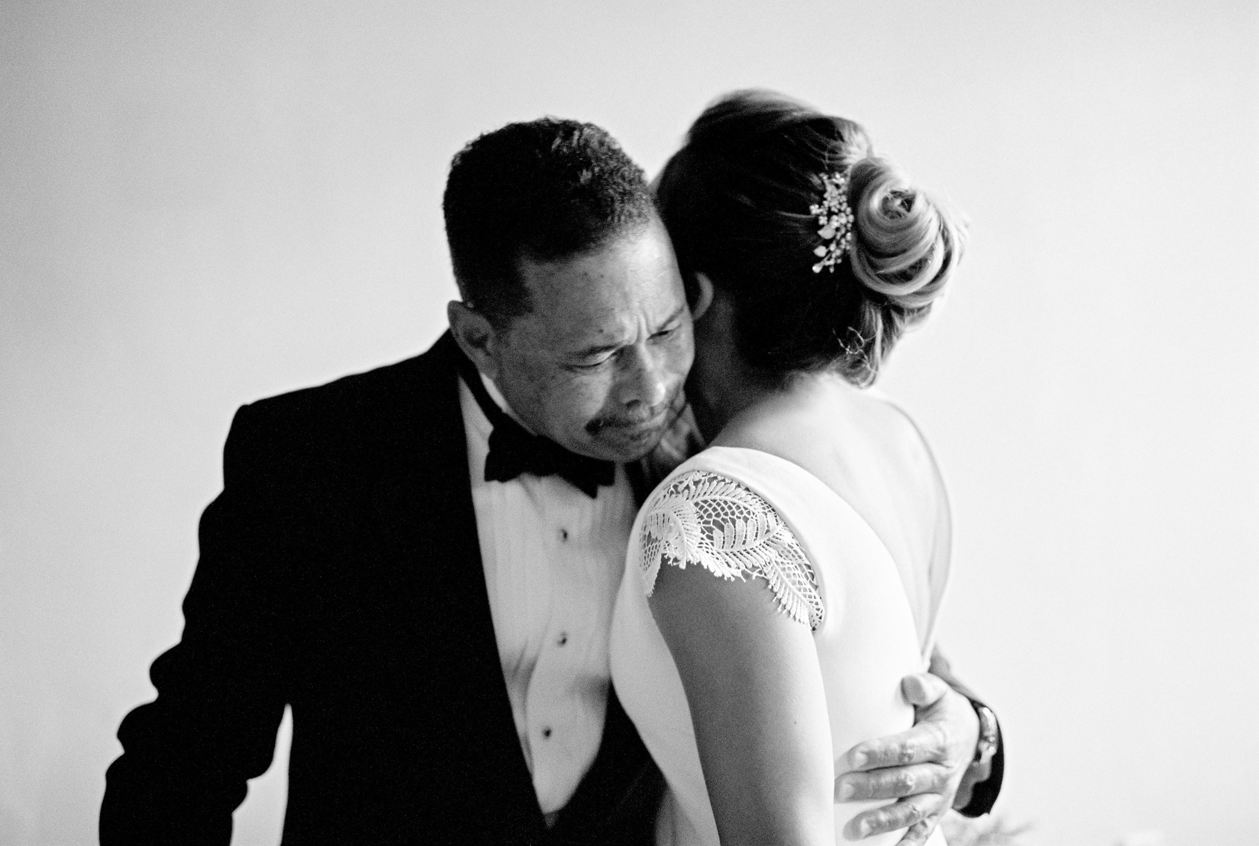 wedding bride and father hug in formal attire