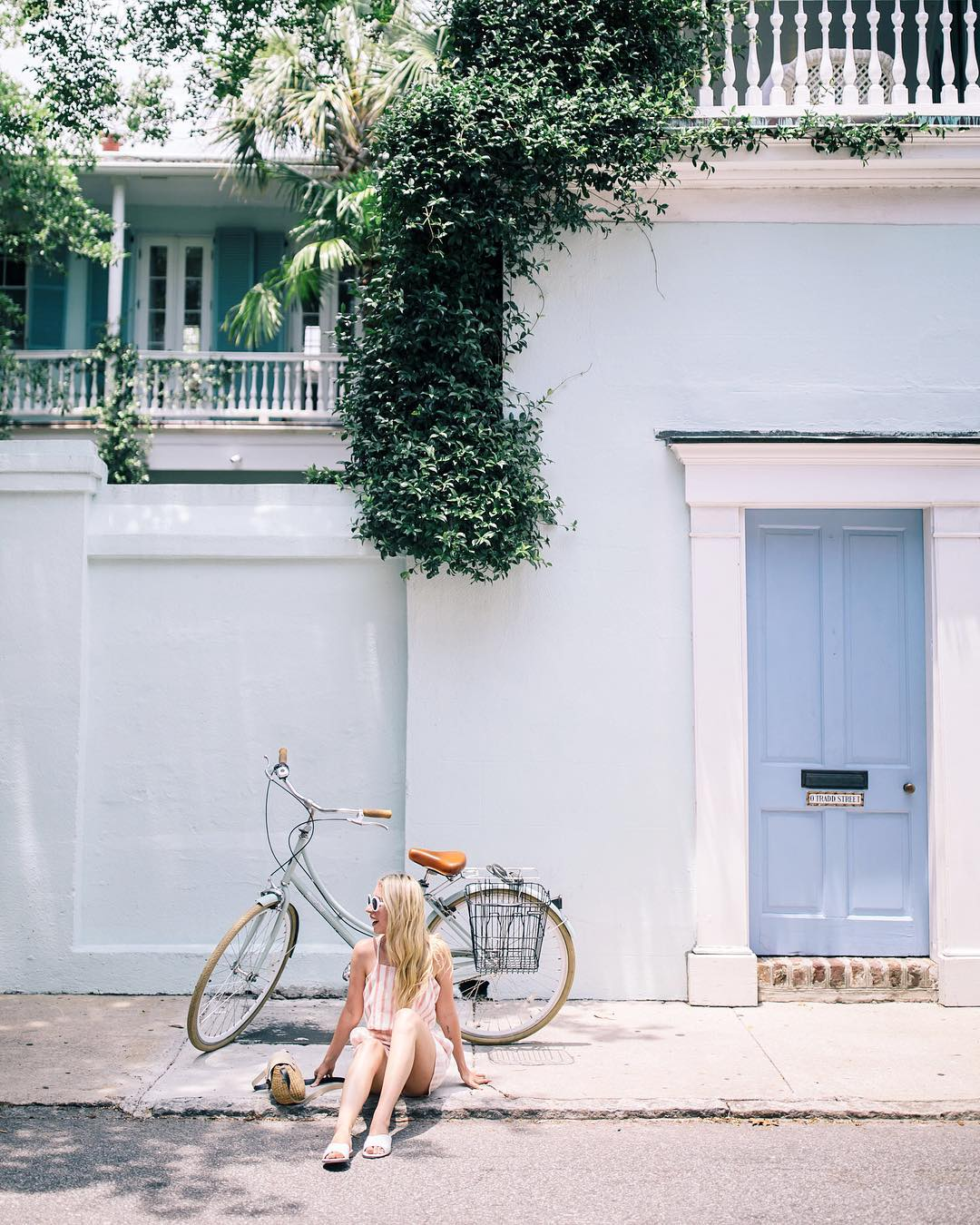 bachelorette cities charleston women sitting by bike on curb in front of blue building