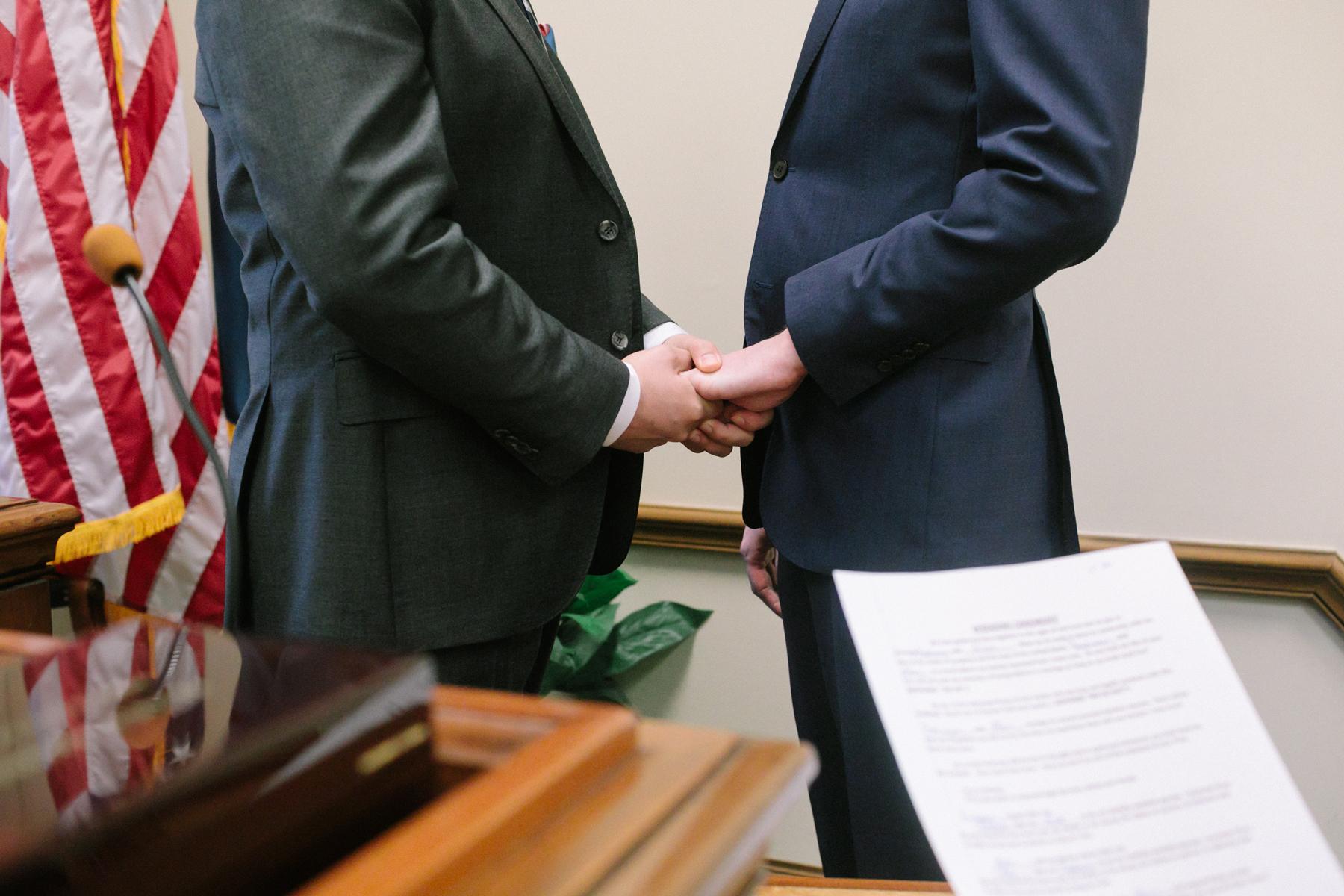 city hall wedding grooms holding hands