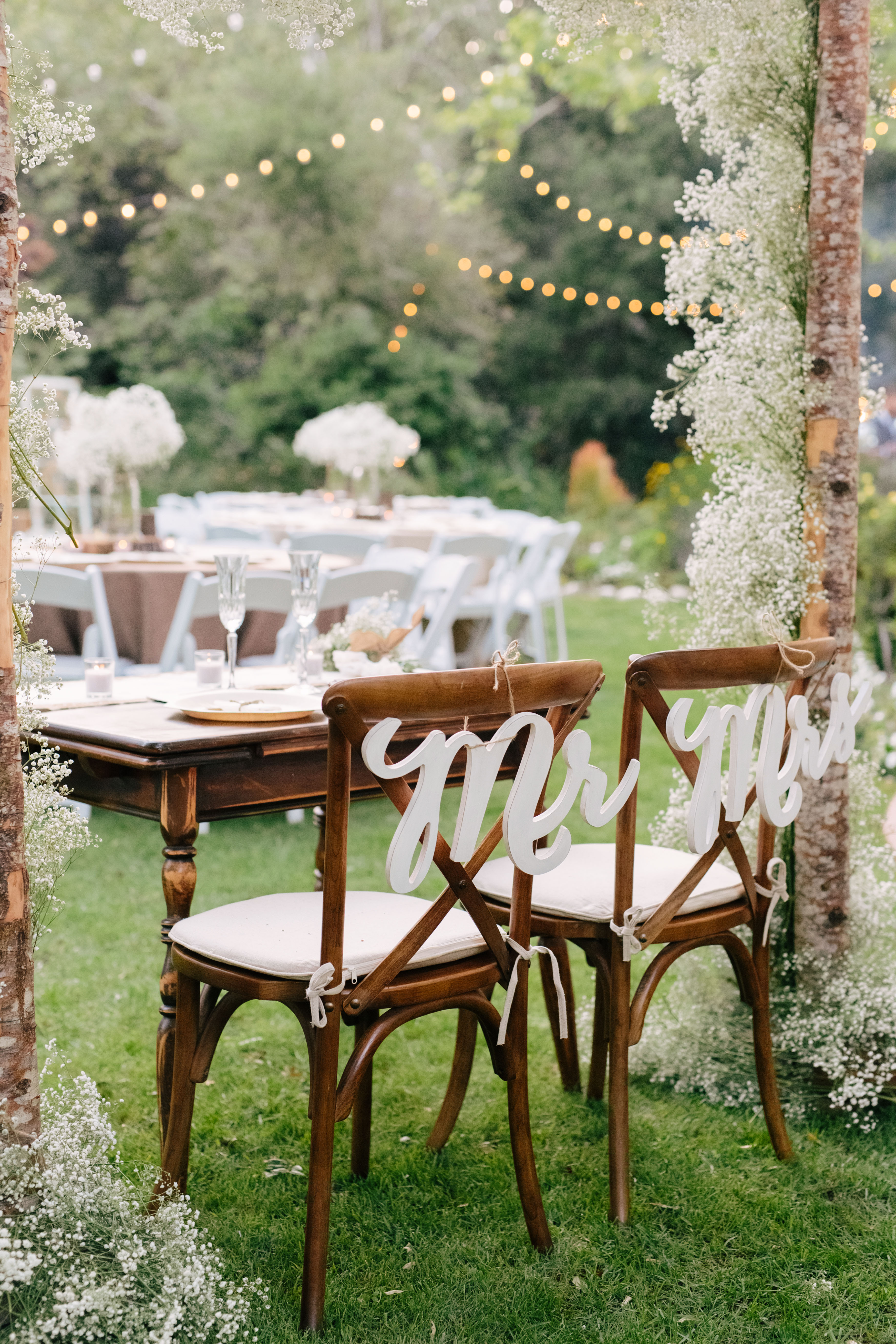mr and mrs white signs tied with twine to chairs