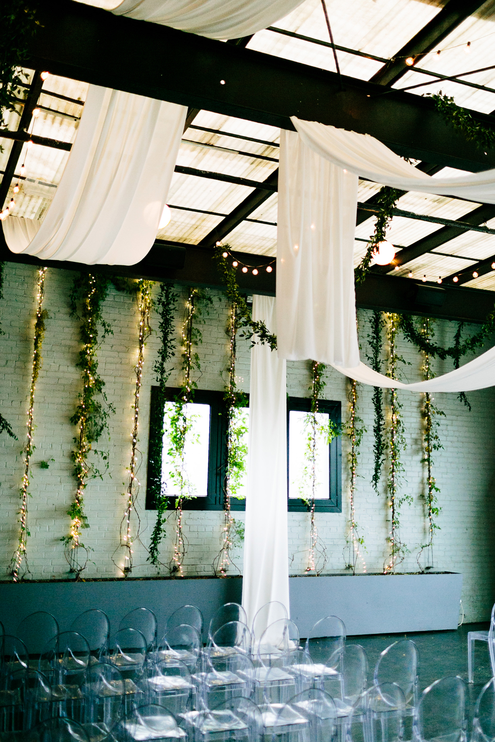 twinkle lights intertwined with ivy against ceremony wall