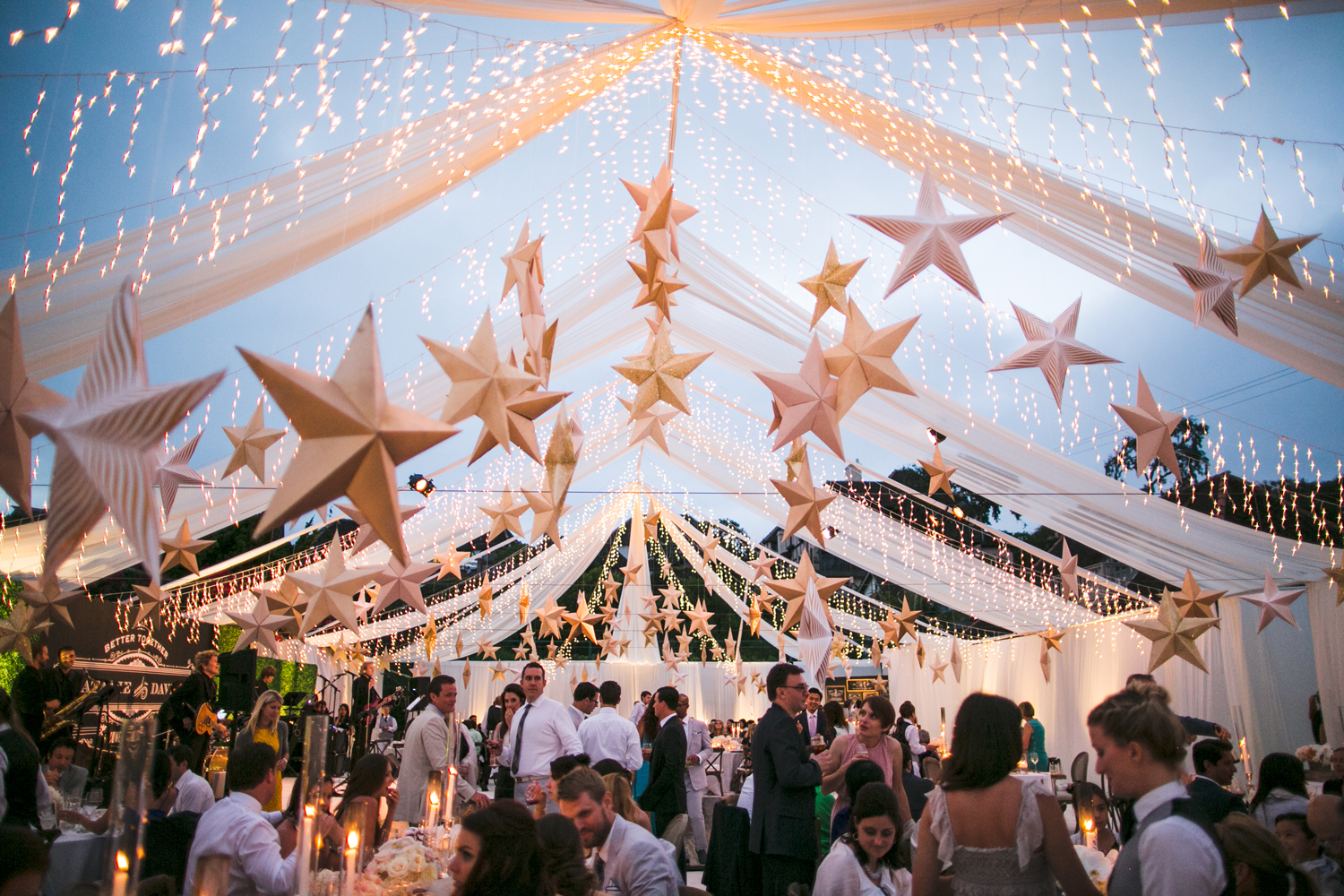 twinkle lights cascading on open air tent ceiling with dimensional stars