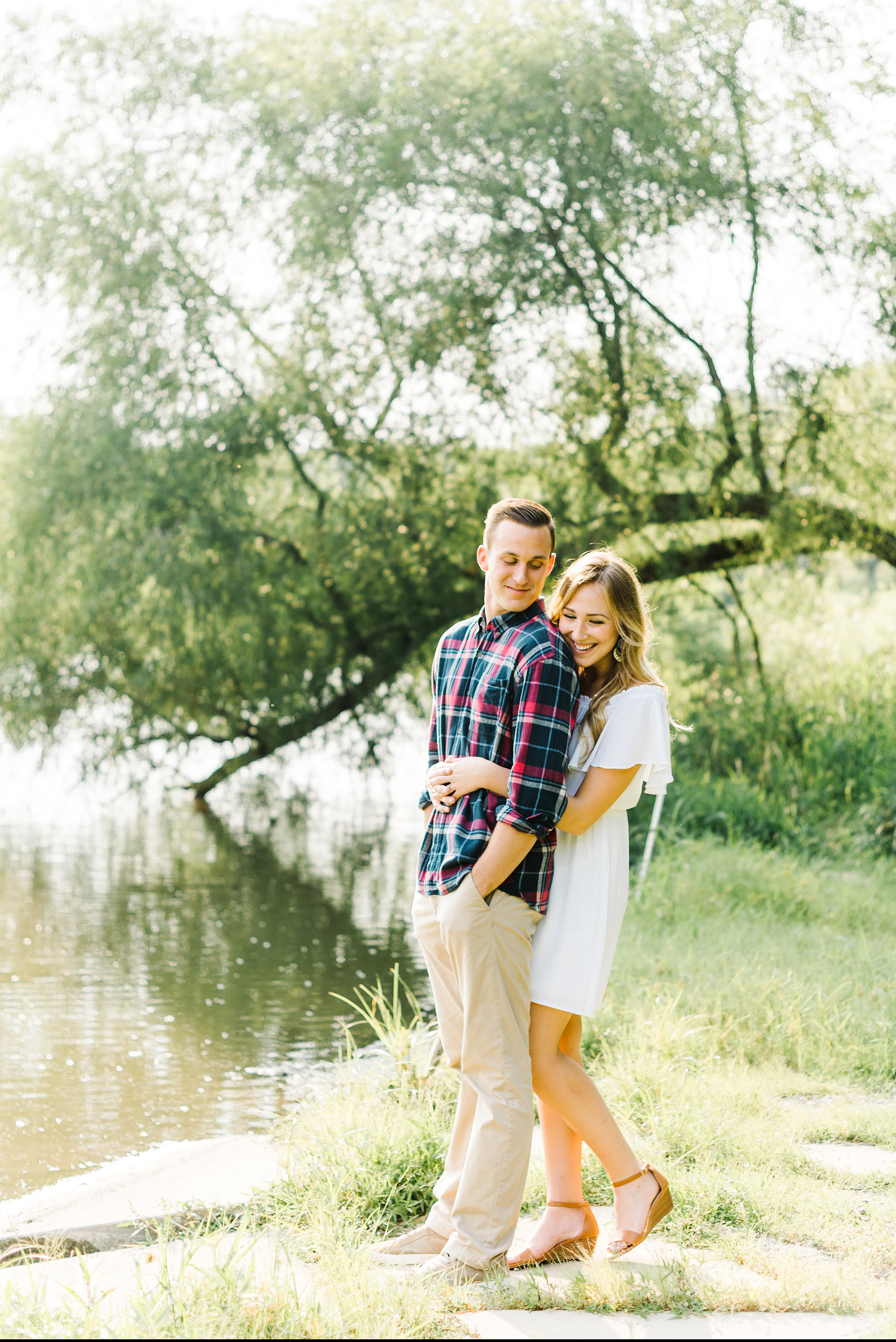 couple hugging under tree engagement photo