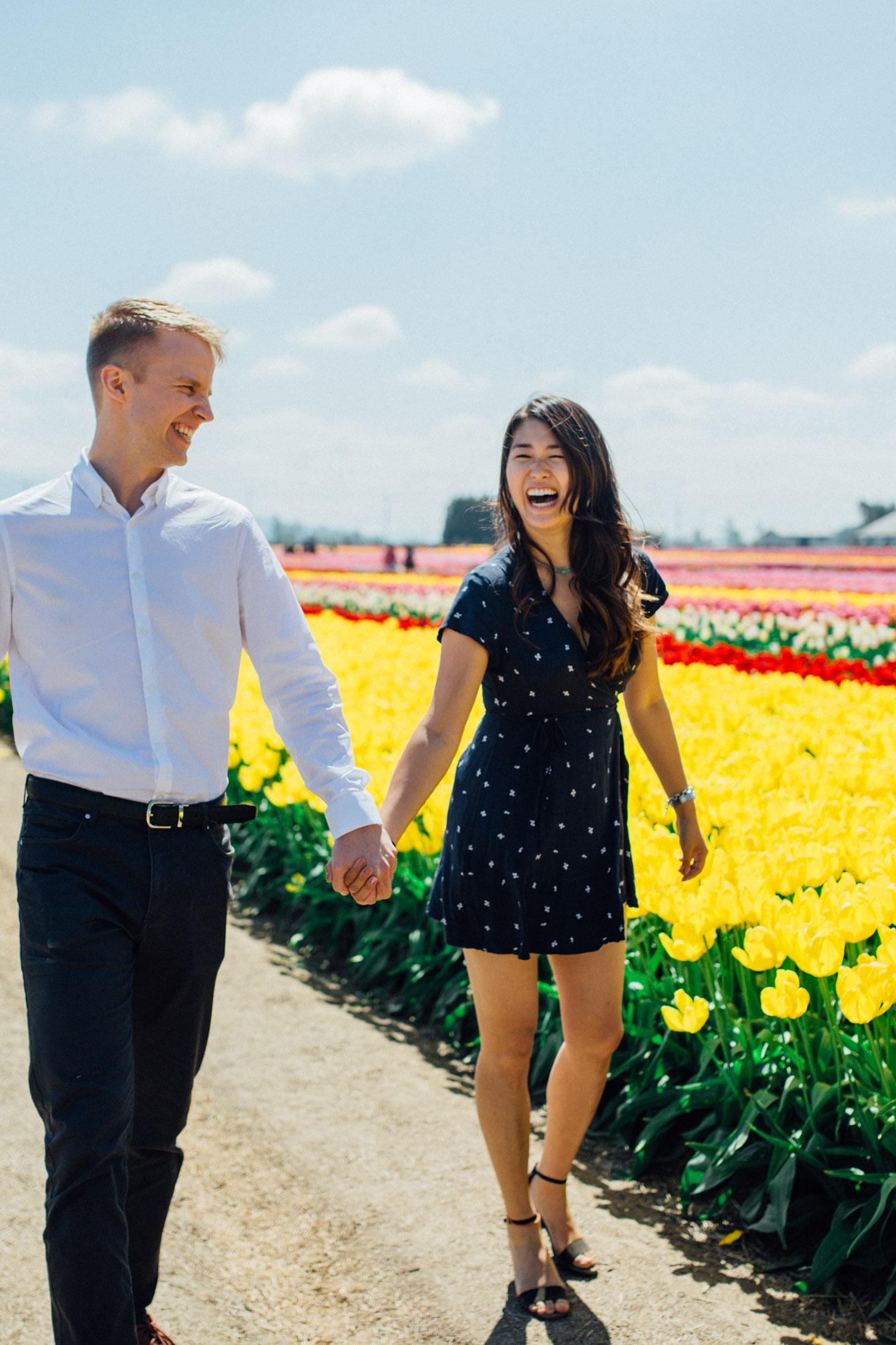 couple walking in flower field summer engagement photos